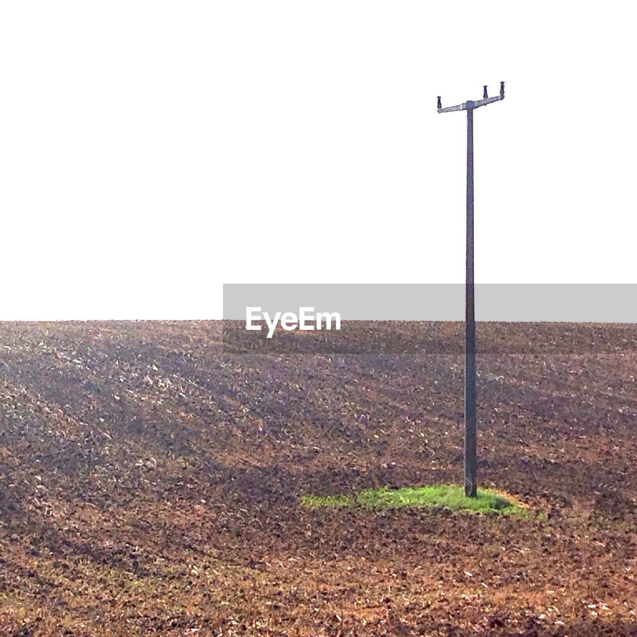 Pole Amidst Field Against Clear Sky