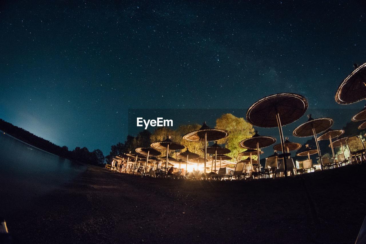 Low Angle Fish-Eye Lens Shot Of Parasols Against Sky At Night