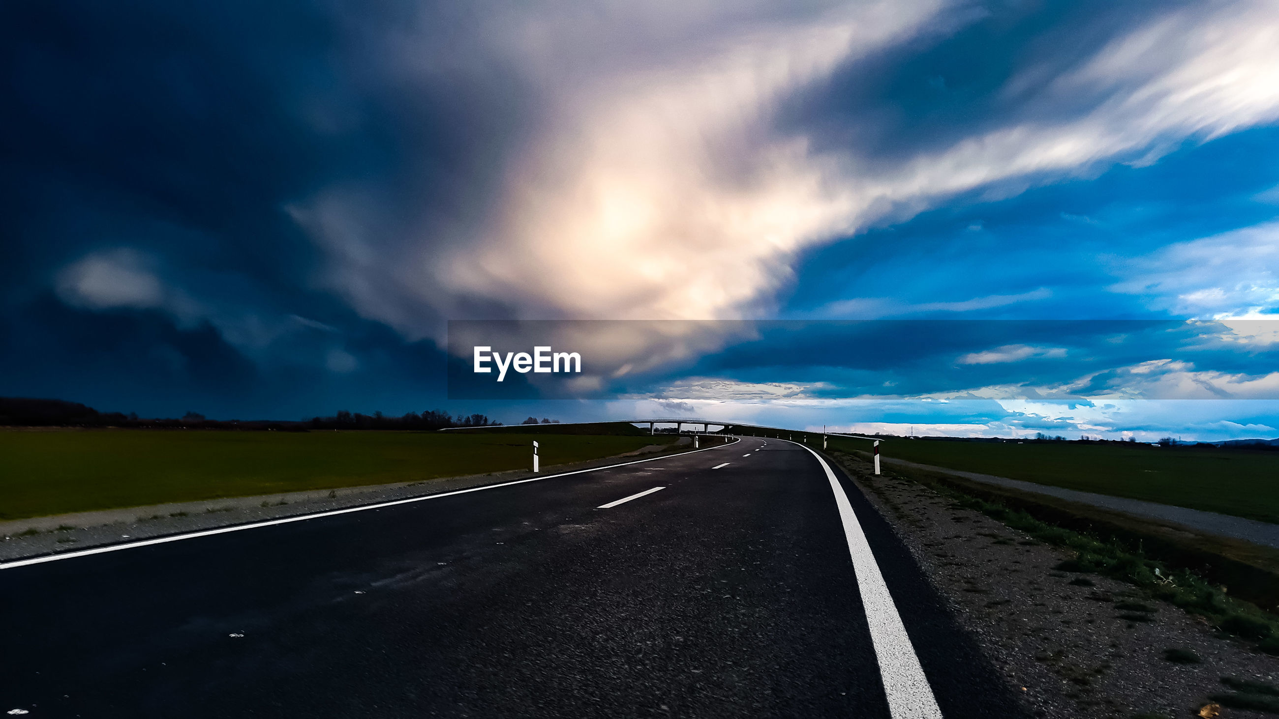 Empty road along countryside landscape against storm clouds