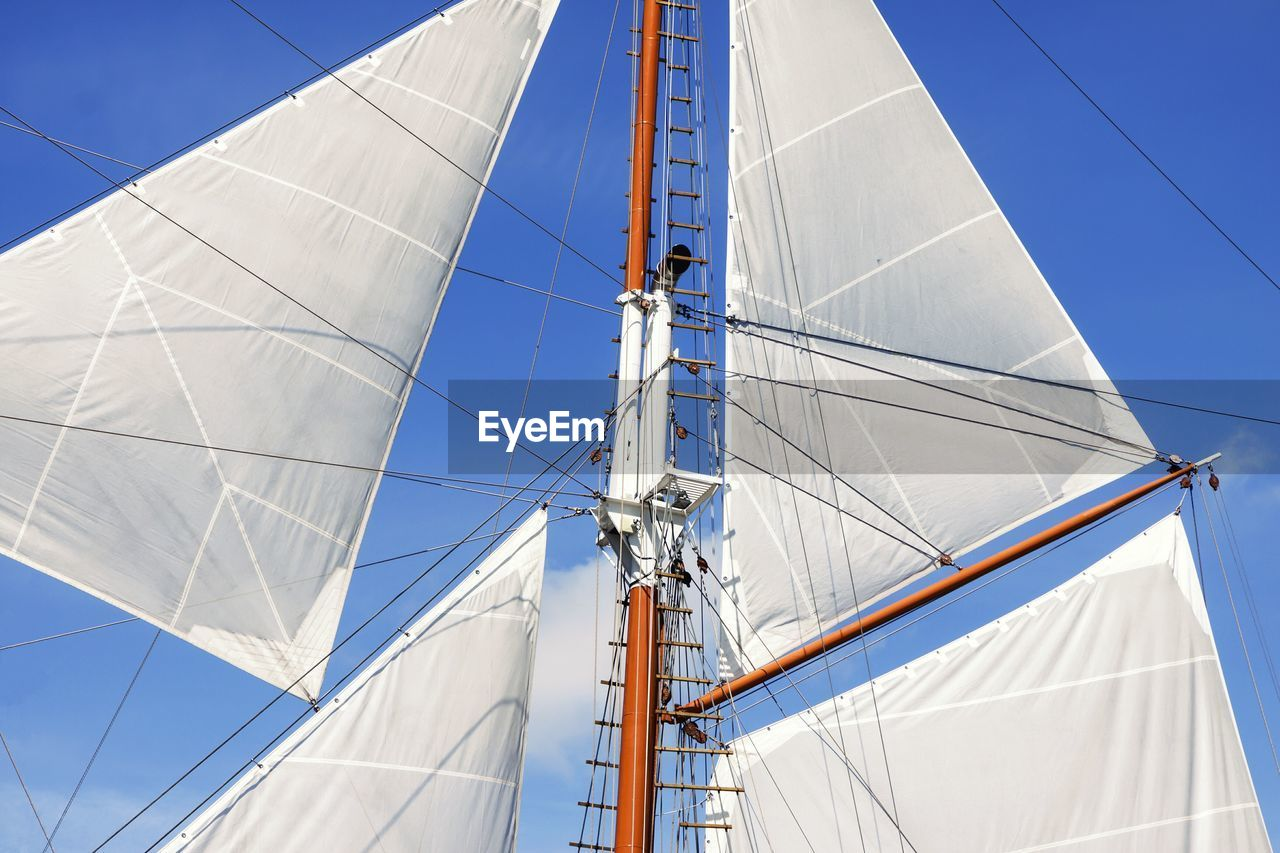 Low Angle View Of Sailboats Against Blue Sky