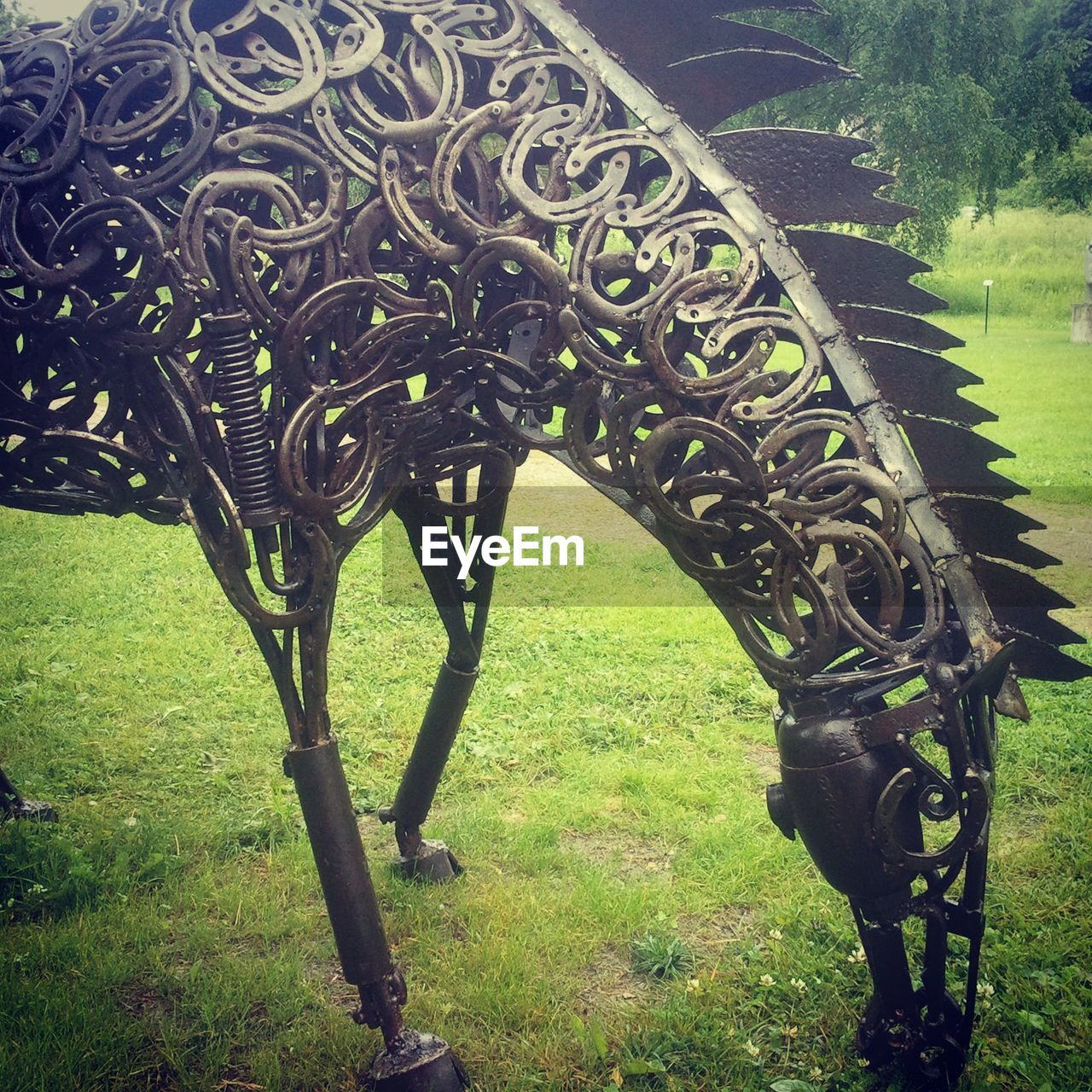 Artificial Horse On Grassy Field In Park