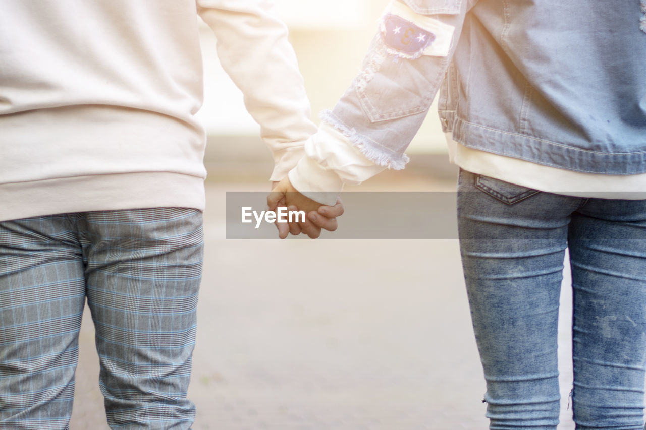 casual clothing, midsection, love, two people, togetherness, men, positive emotion, real people, holding hands, bonding, couple - relationship, emotion, rear view, women, standing, day, jeans, adult, people, leisure activity, outdoors, hand