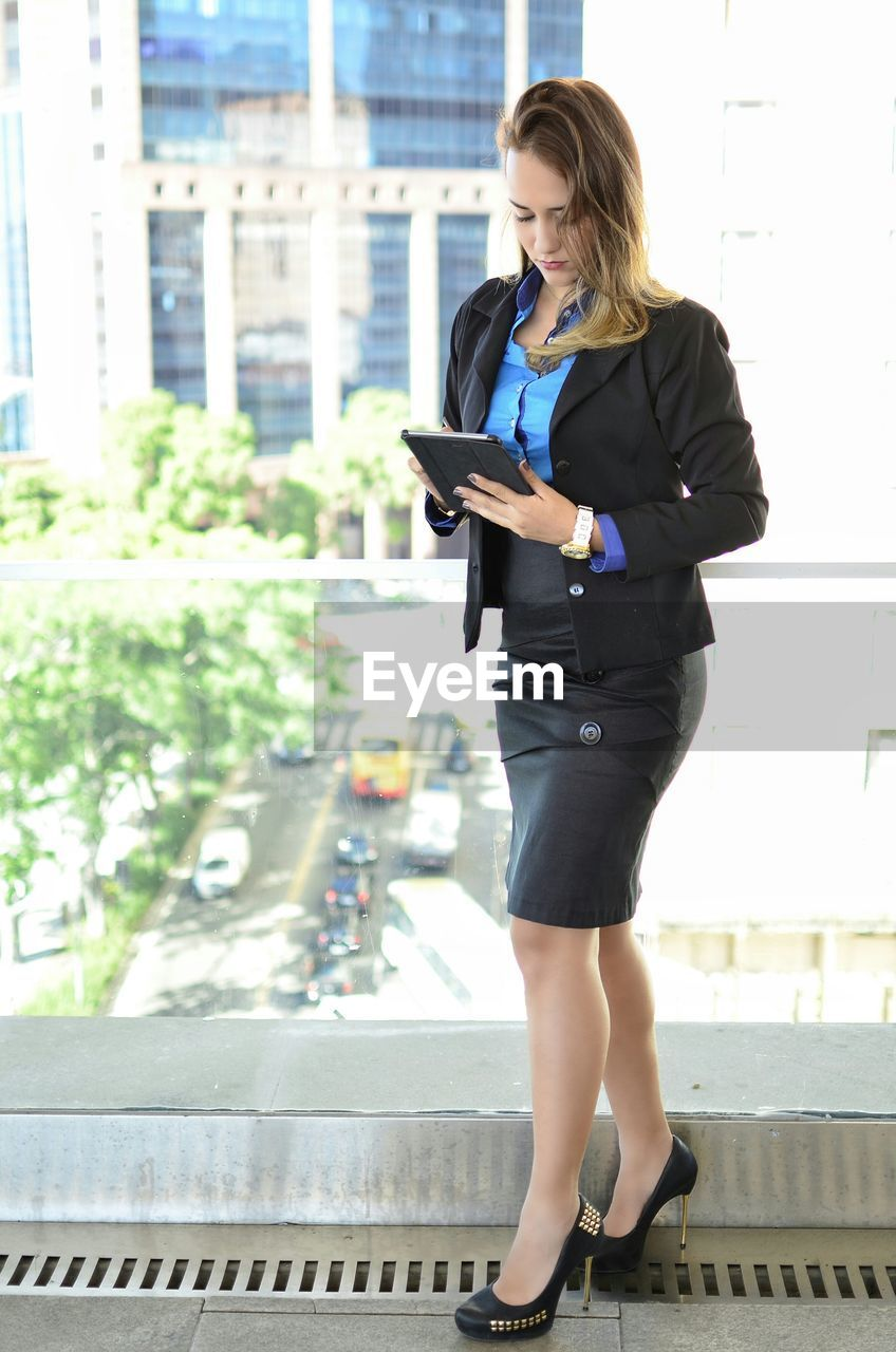 Beautiful businesswoman standing in balcony while using tablet computer