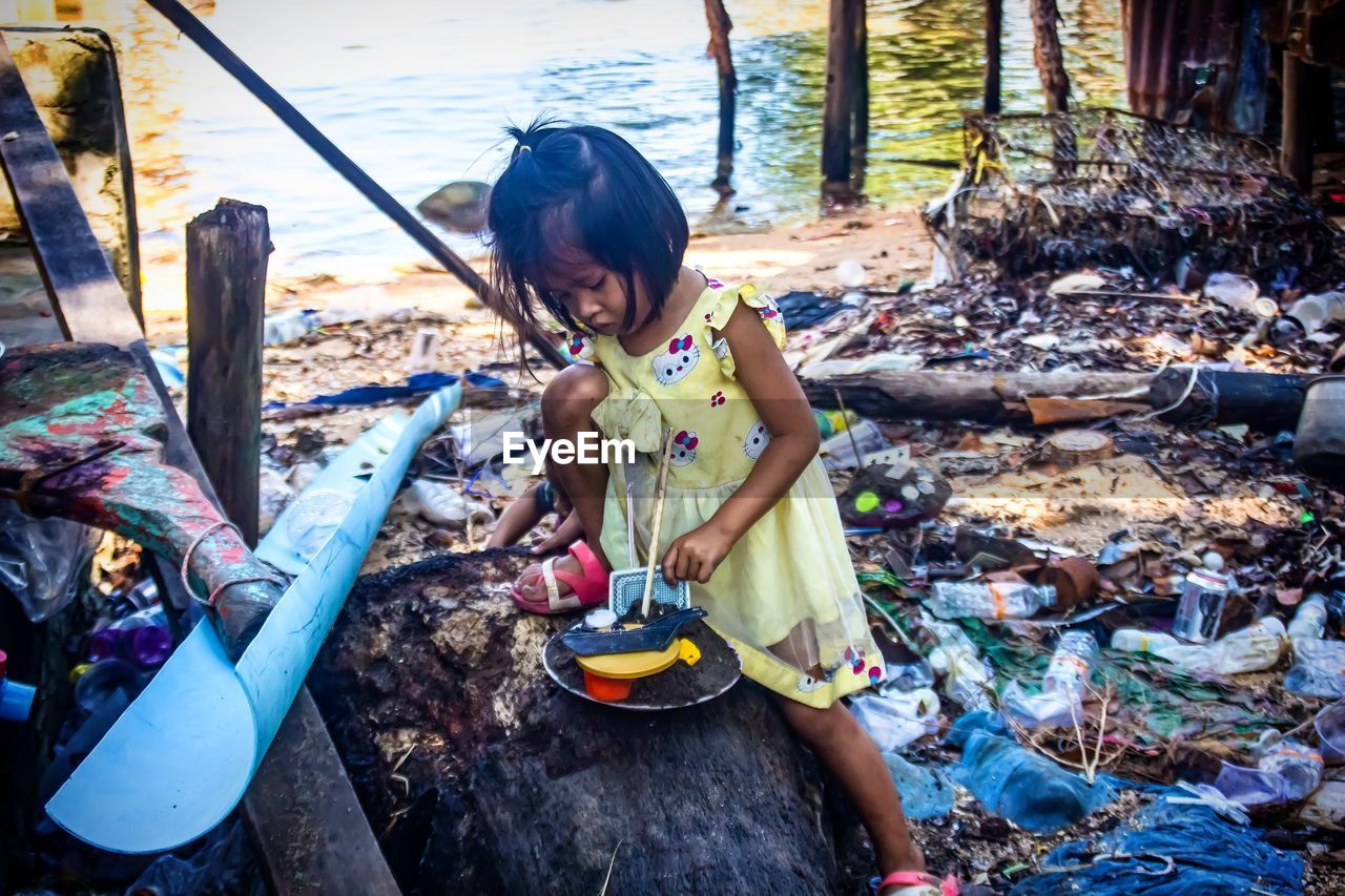 High Angle View Of Girl Playing With Toys While Sitting Outdoors