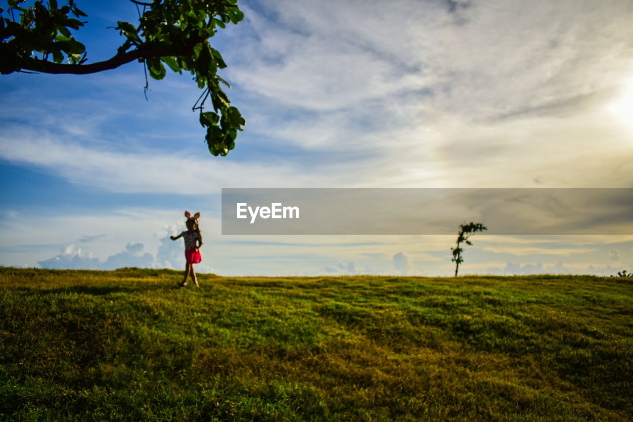 one person, sky, plant, cloud - sky, grass, real people, land, leisure activity, green color, lifestyles, field, full length, nature, standing, beauty in nature, adult, women, tree, landscape, outdoors