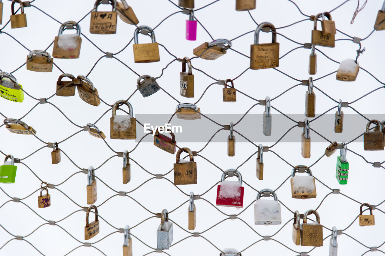 Padlocks Attached To Chainlink Fence During Winter