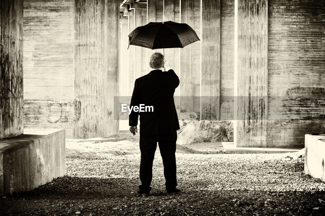 REAR VIEW OF MAN WITH UMBRELLA WALKING ON RAINY DAY