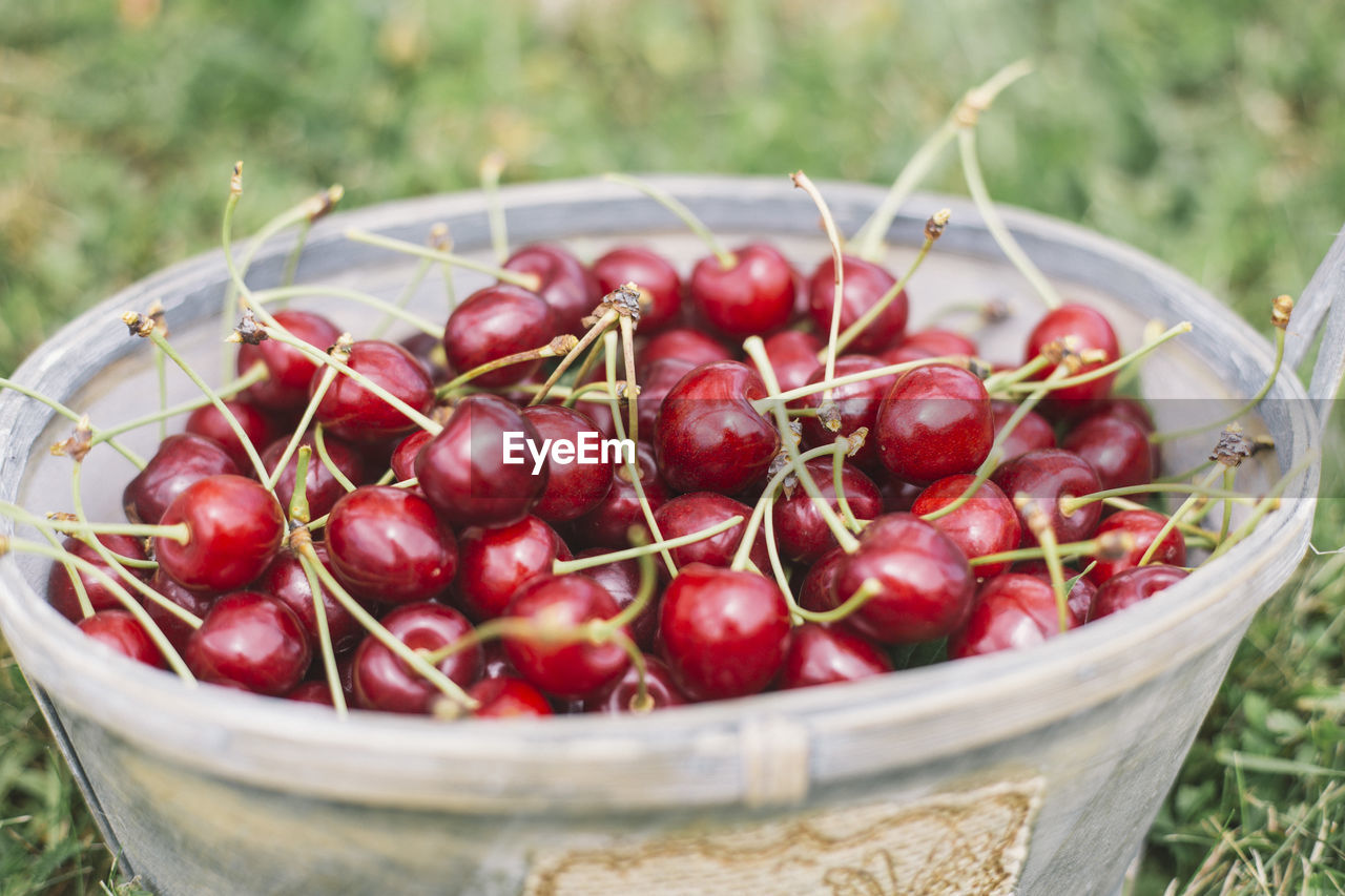 CLOSE-UP OF RED CHERRIES IN BASKET