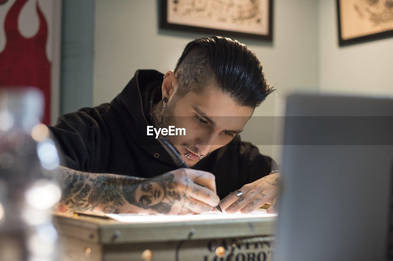 Male tattoo artist drawing design on paper at studio