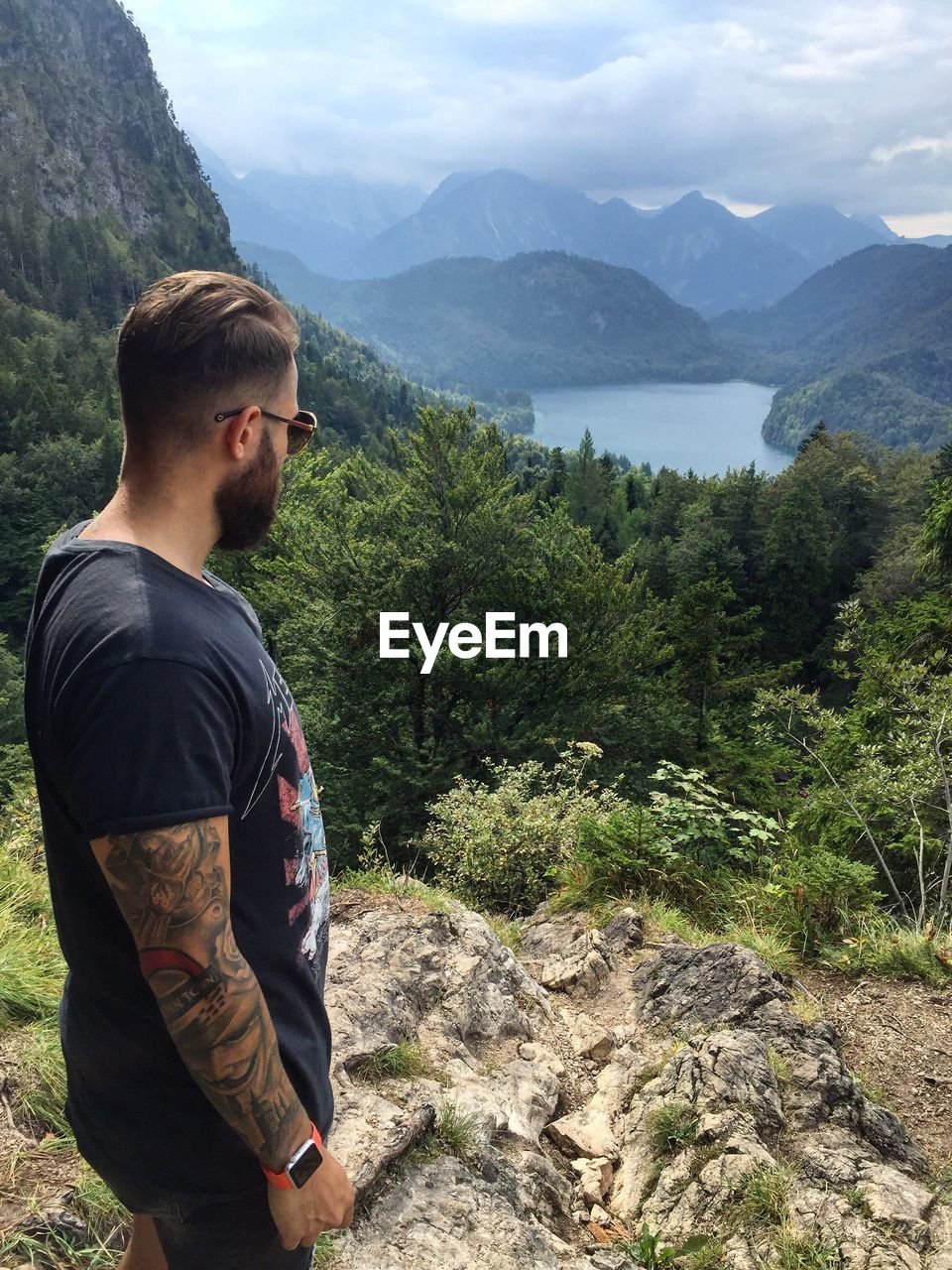 Man Looking At River And Mountains Against Cloudy Sky