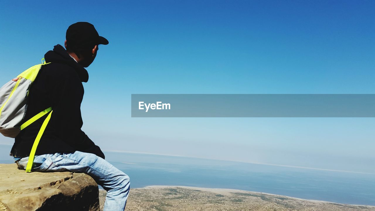 sea, water, real people, sky, one person, leisure activity, lifestyles, scenics - nature, beauty in nature, blue, nature, horizon, men, horizon over water, day, clear sky, copy space, casual clothing, looking at view, outdoors
