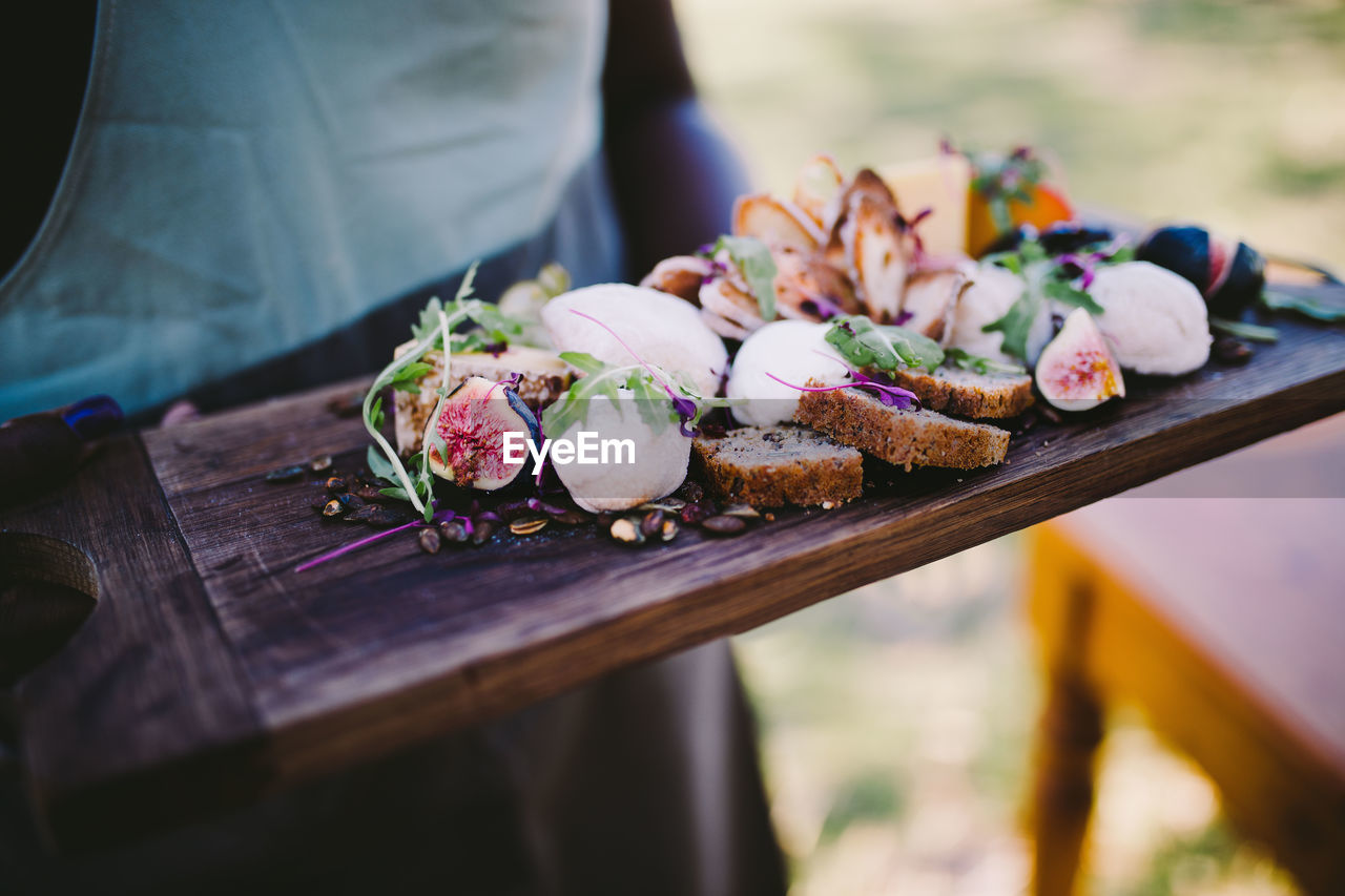 Midsection Of Person With Various Fresh Food On Wooden Tray