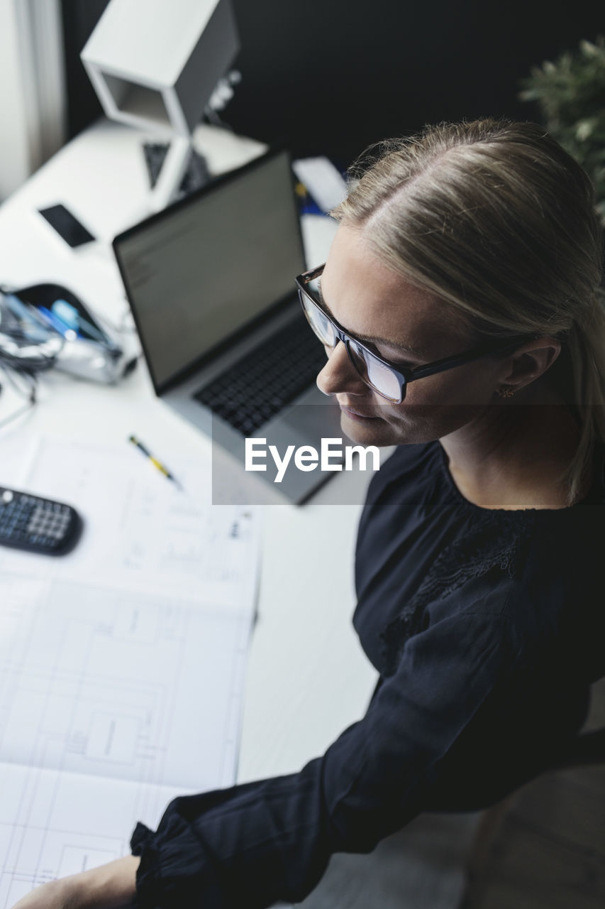 one person, technology, computer, working, real people, office, table, women, connection, business, sitting, concentration, business person, adult, glasses, indoors, eyeglasses, wireless technology, communication, using laptop