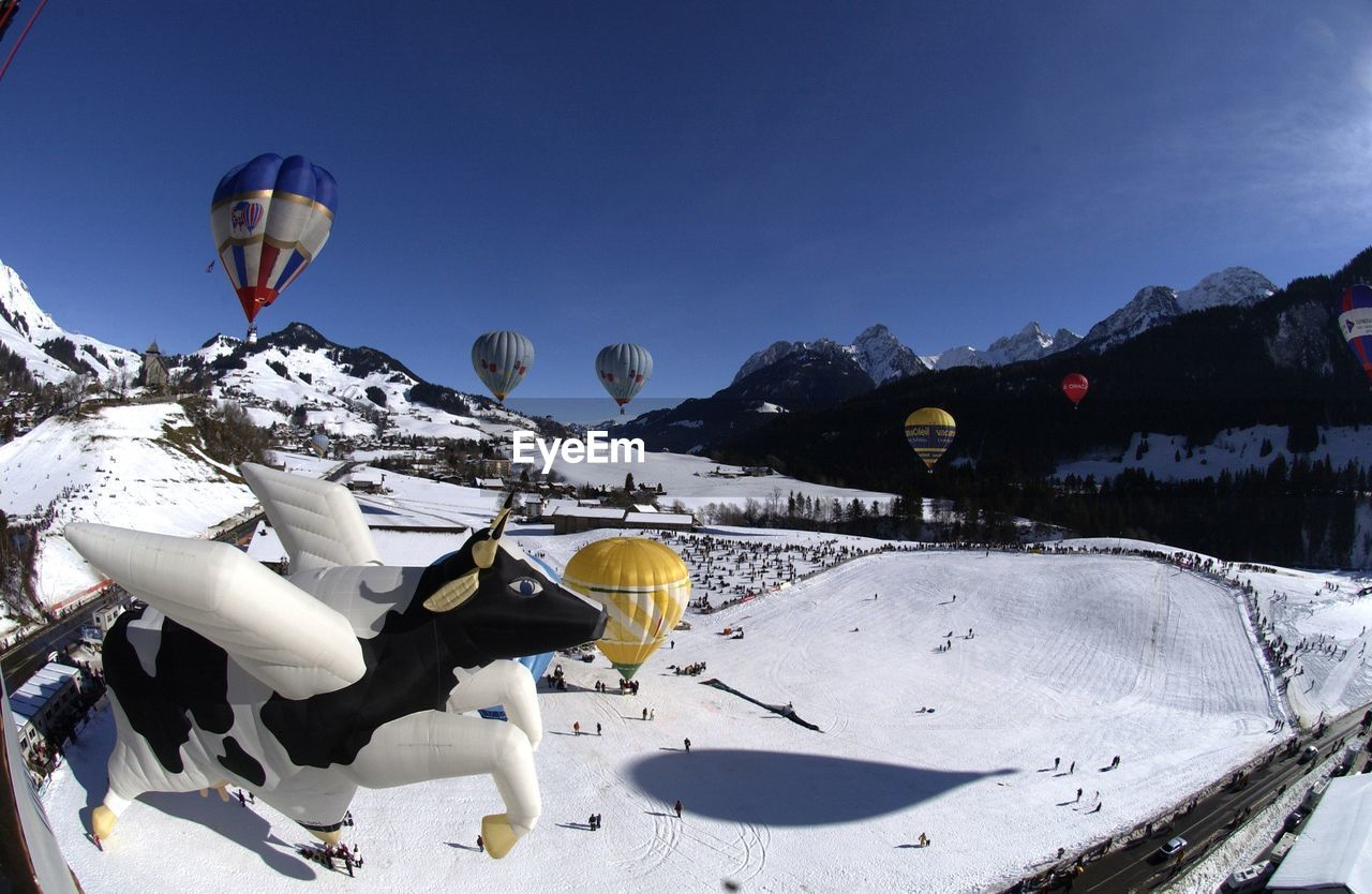 snow, mountain, cold temperature, winter, outdoors, nature, day, mountain range, transportation, mid-air, adventure, sky, scenics, no people, beauty in nature, clear sky, extreme sports