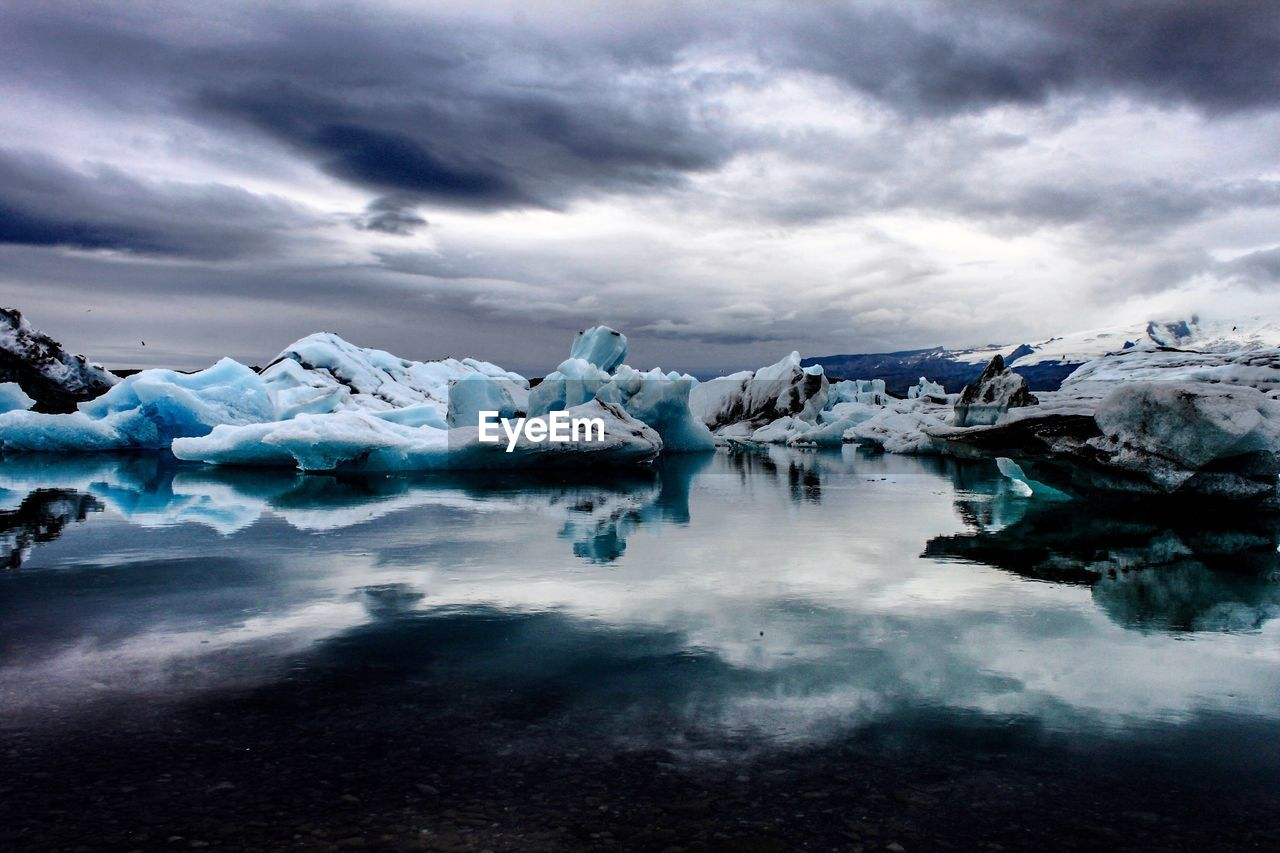 Scenic view of icebergs against dramatic sky