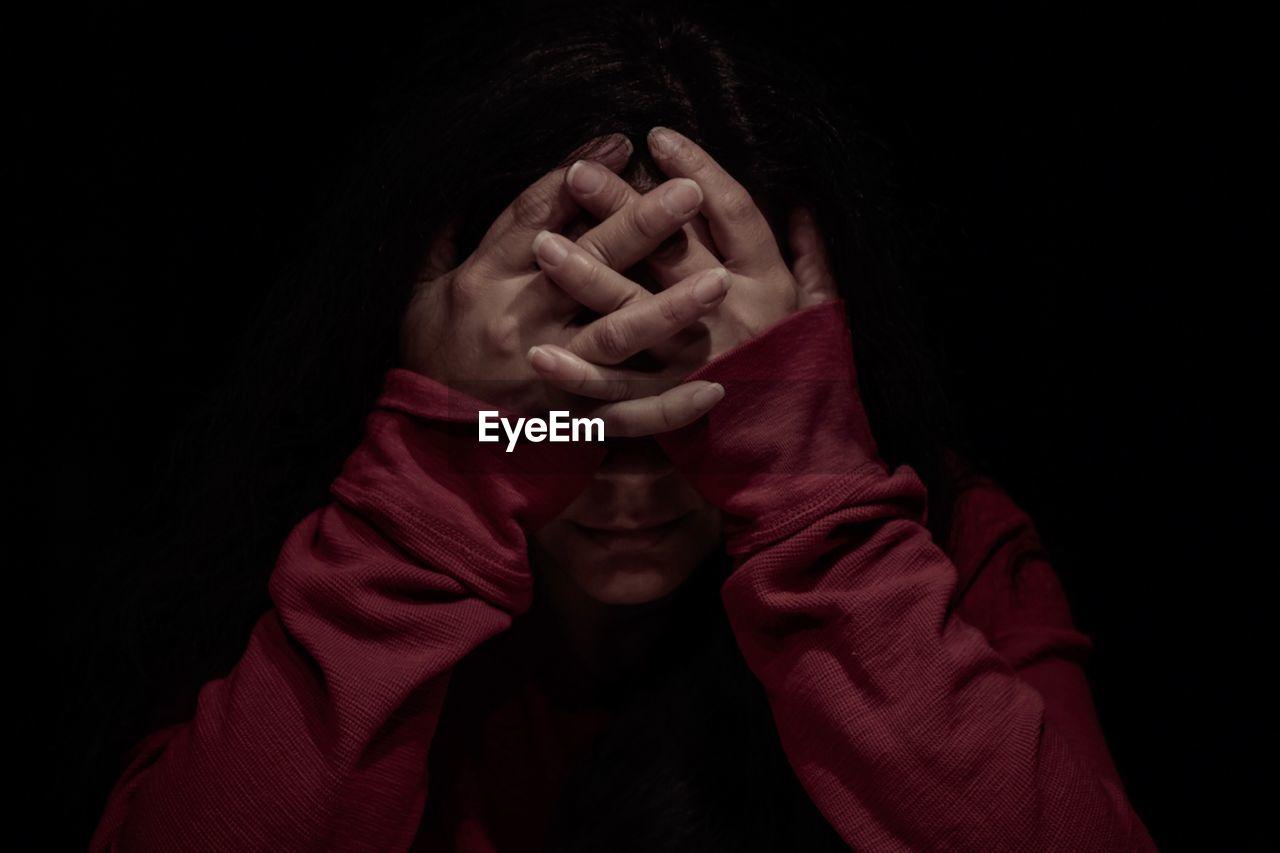 Woman With Head In Hands In Darkroom