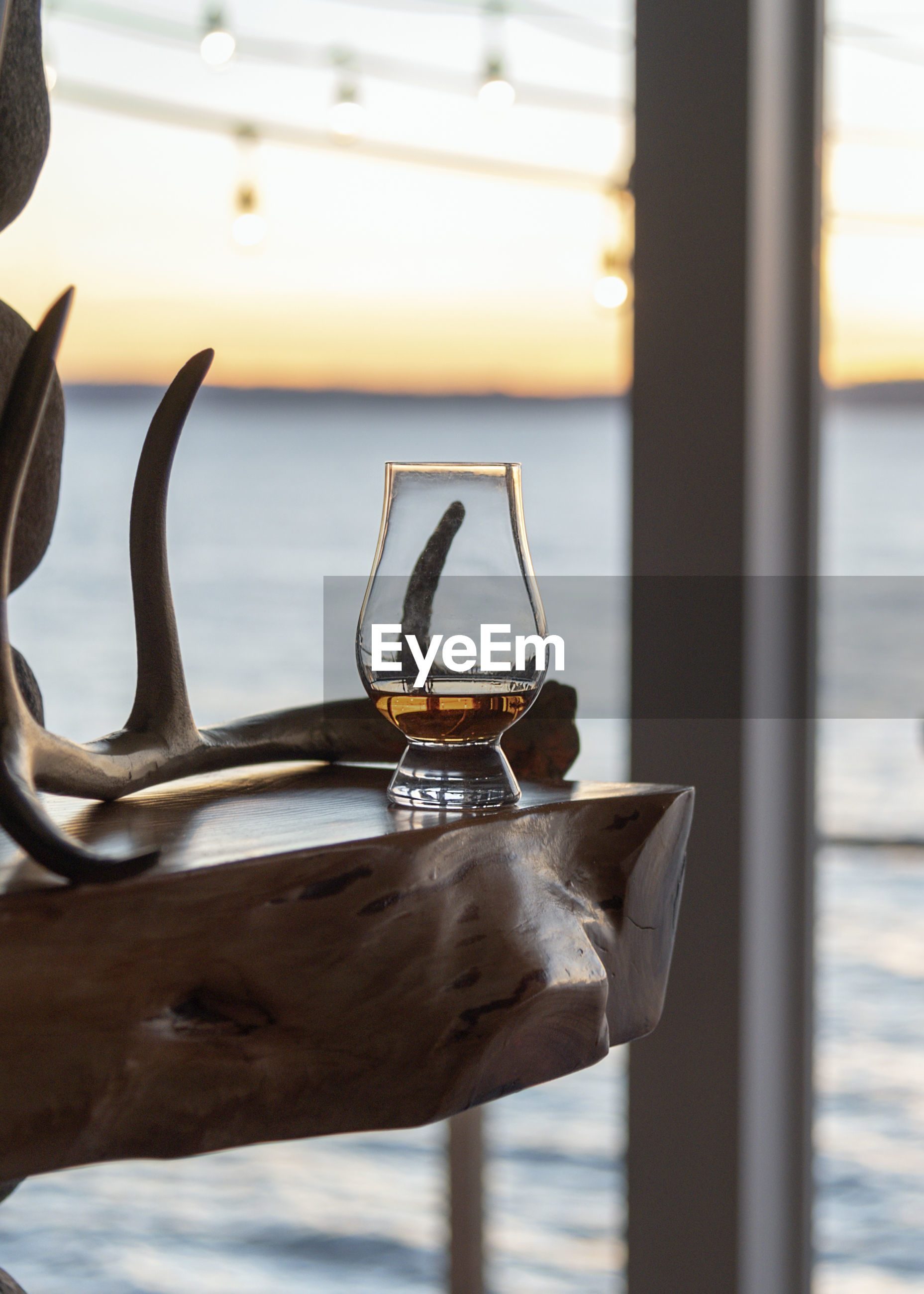 Close-up of drink in glass on table by window against sea during sunset