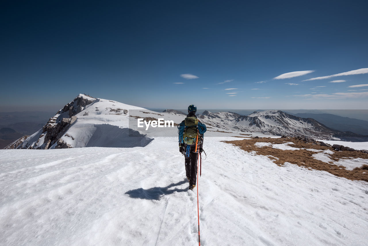 Rear view of man walking on snow covered mountain against sky