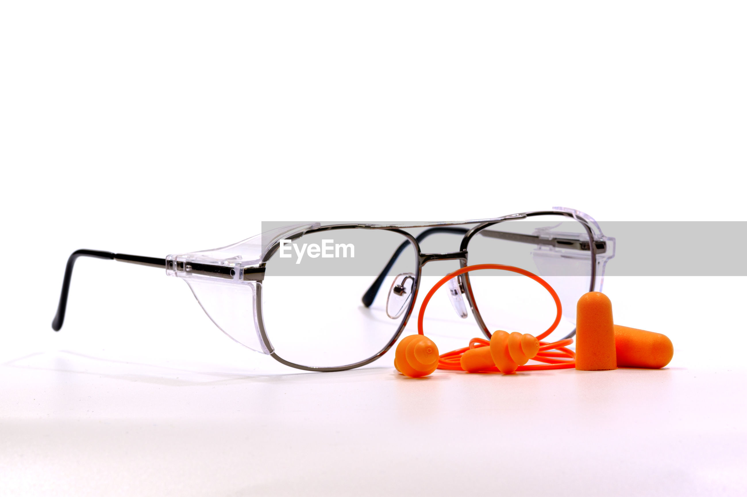 Close-up of eyeglasses with in-ear headphones against white background