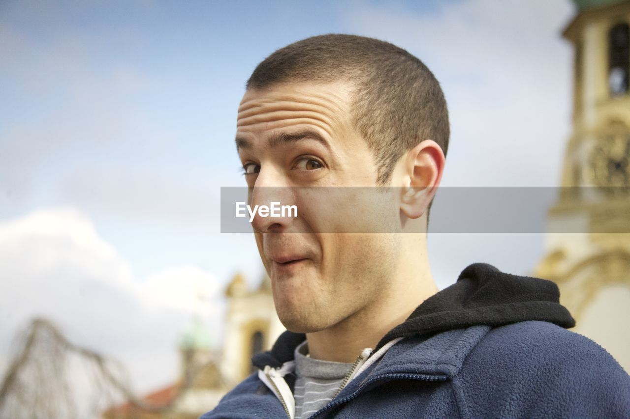 Portrait of young man making face while standing outdoors