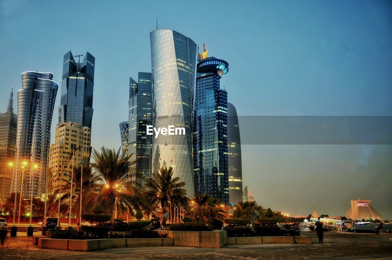 built structure, building exterior, architecture, sky, city, office building exterior, building, skyscraper, water, nature, tall - high, modern, tree, tower, no people, office, urban skyline, illuminated, tropical climate, outdoors, cityscape, financial district
