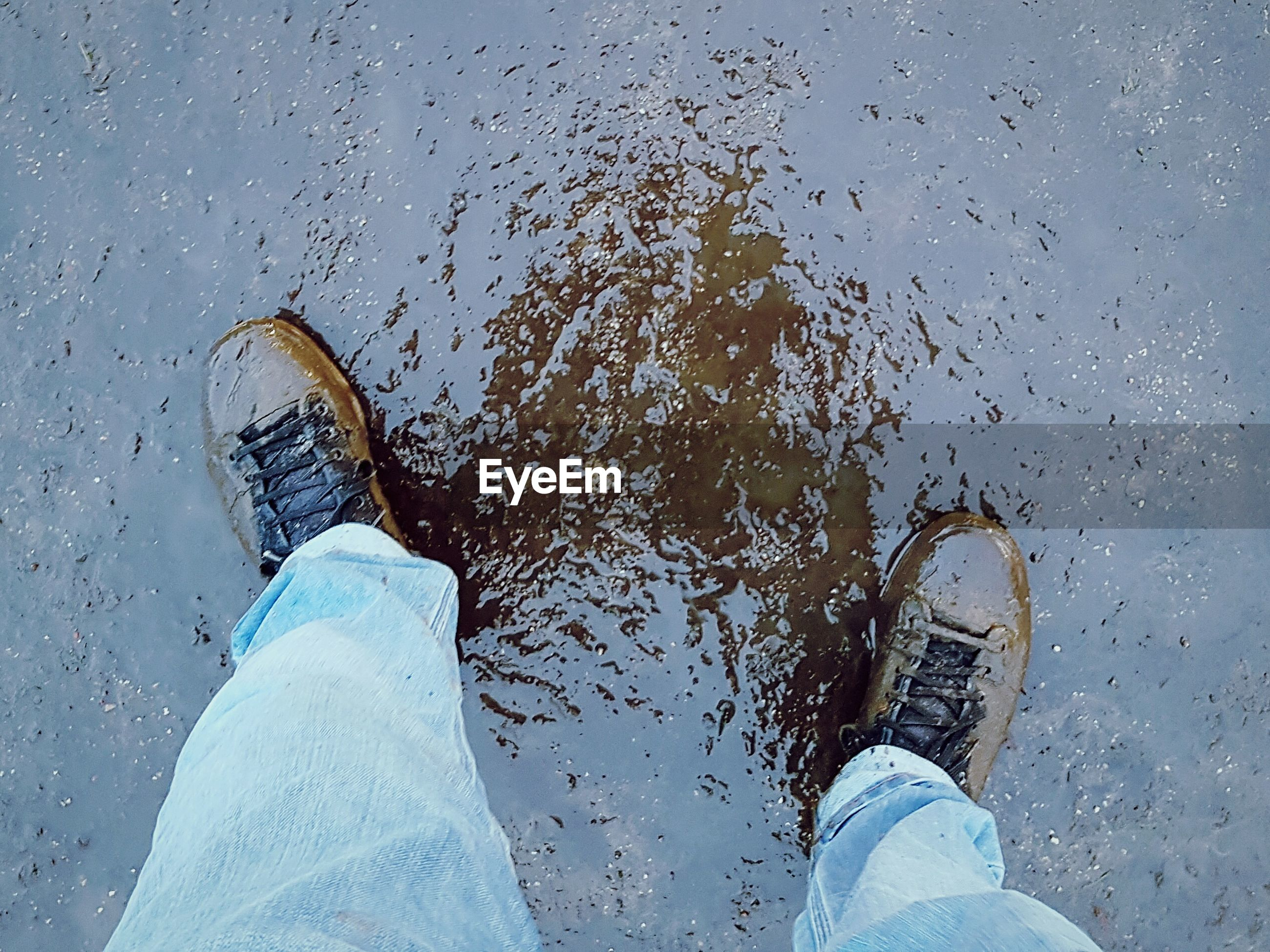 low section, human leg, personal perspective, real people, water, one person, human foot, lifestyles, shoe, standing, leisure activity, day, human body part, men, outdoors, beach, nature, sea, puddle, close-up, sky, people