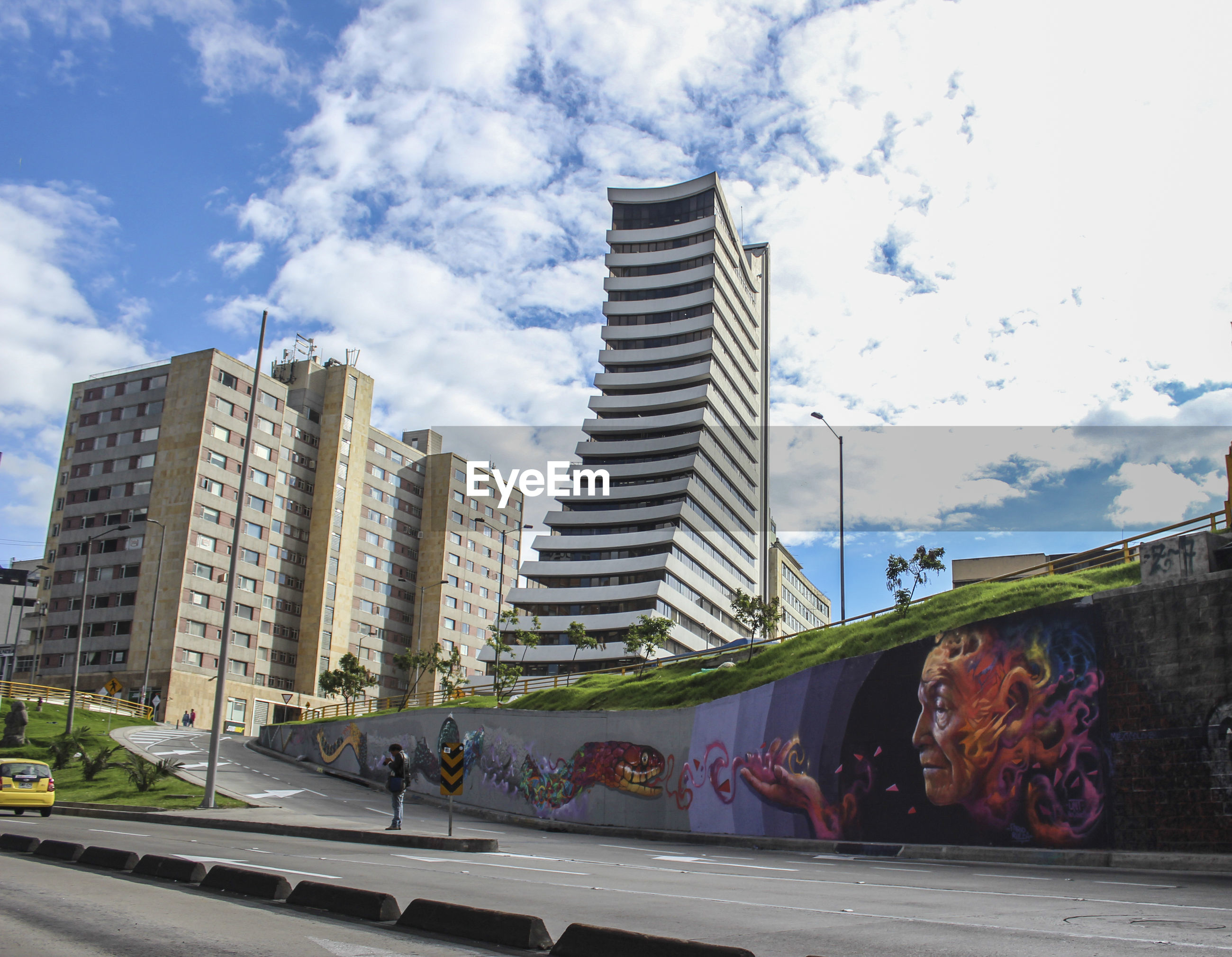 building exterior, architecture, built structure, sky, city, low angle view, building, cloud - sky, cloud, day, modern, outdoors, art, art and craft, office building, no people, skyscraper, city life, street, cloudy