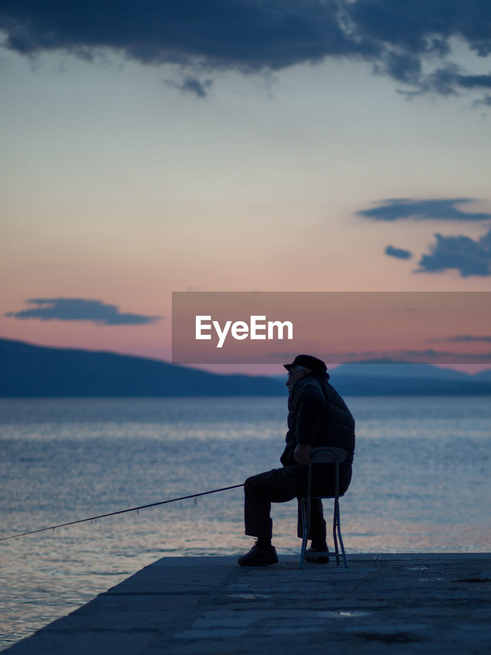 Man sitting on shore against sky during sunset