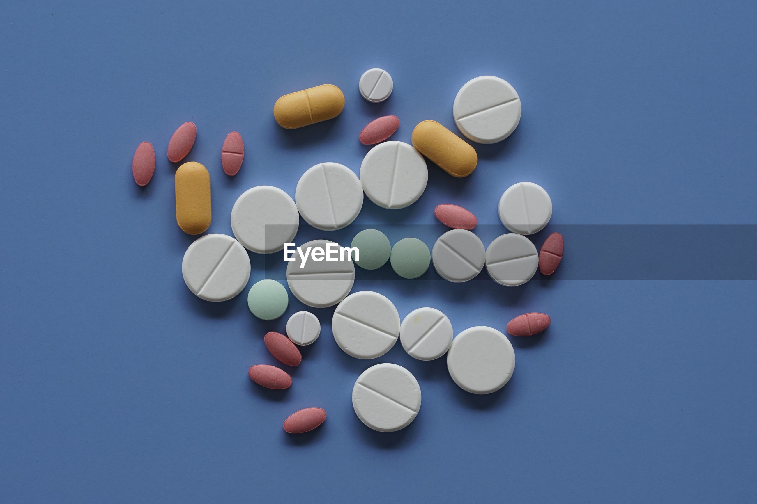 High angle view of colored pills over blue background
