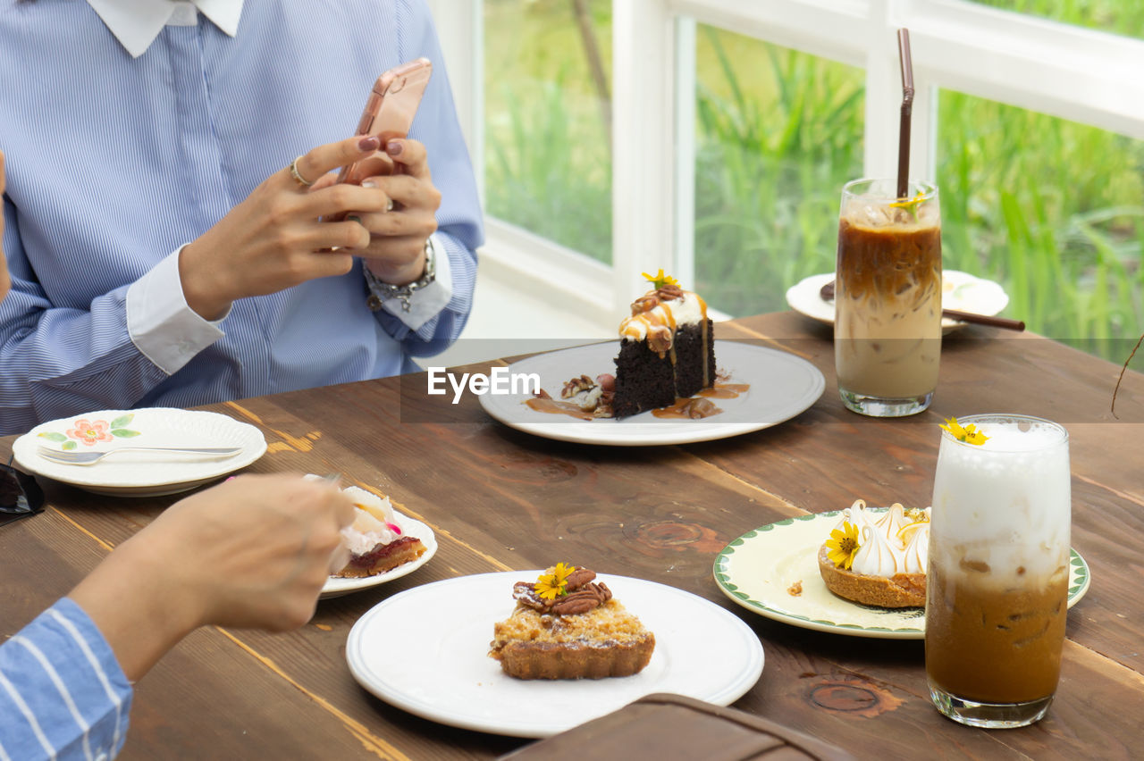 food and drink, food, table, plate, real people, one person, freshness, sweet food, ready-to-eat, sweet, dessert, indoors, human hand, lifestyles, hand, midsection, indulgence, baked, temptation, unhealthy eating, meal, glass