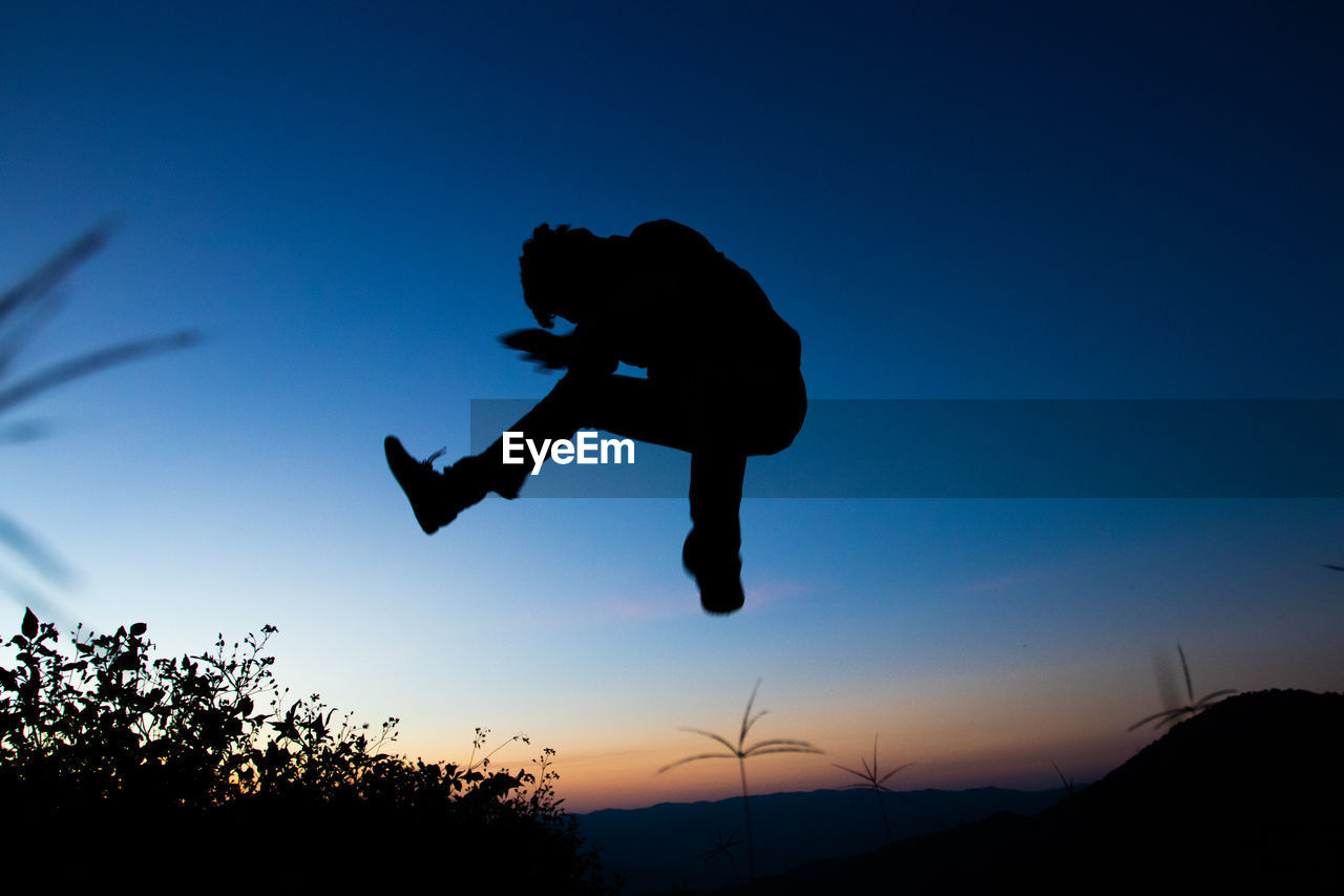 Side view of silhouette man jumping against sky during sunset