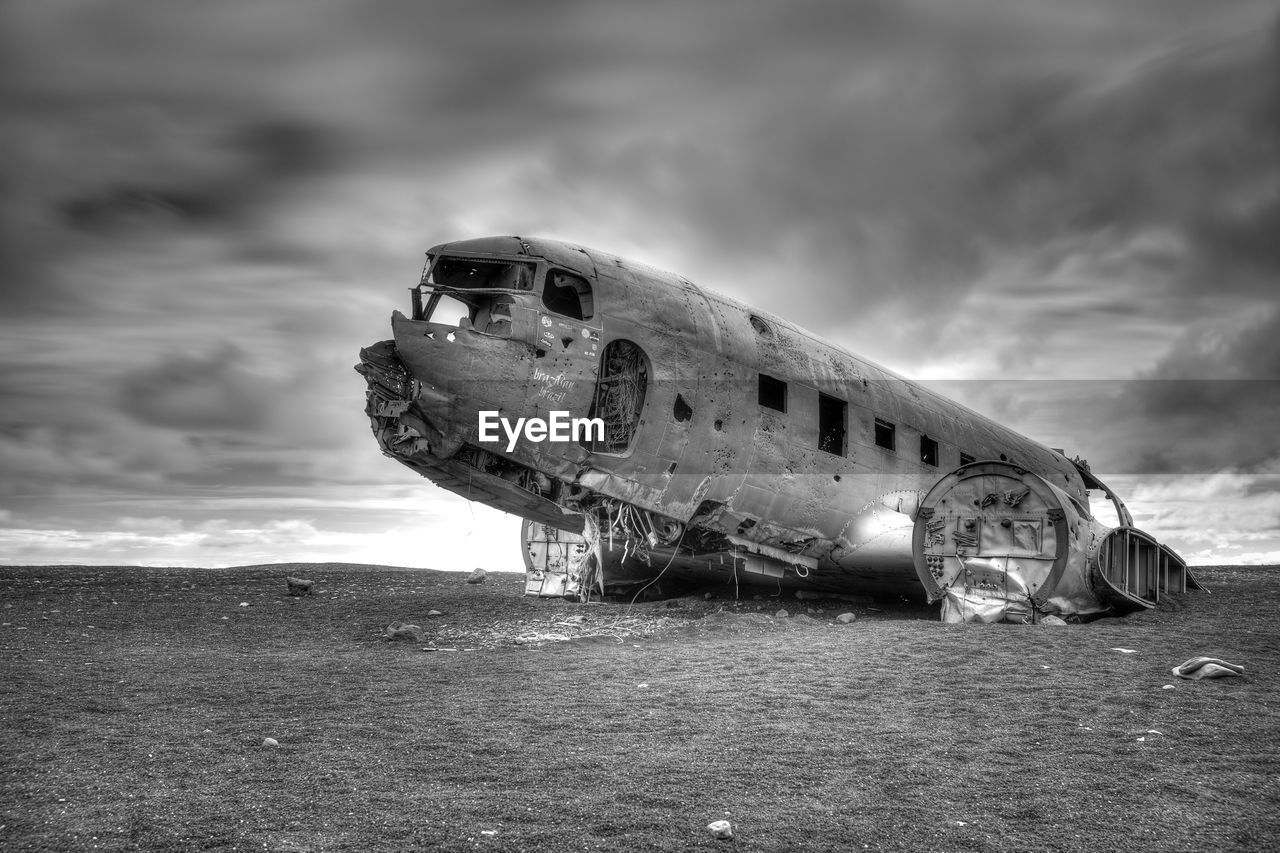 Crashed Airplane On Field Against Cloudy Sky