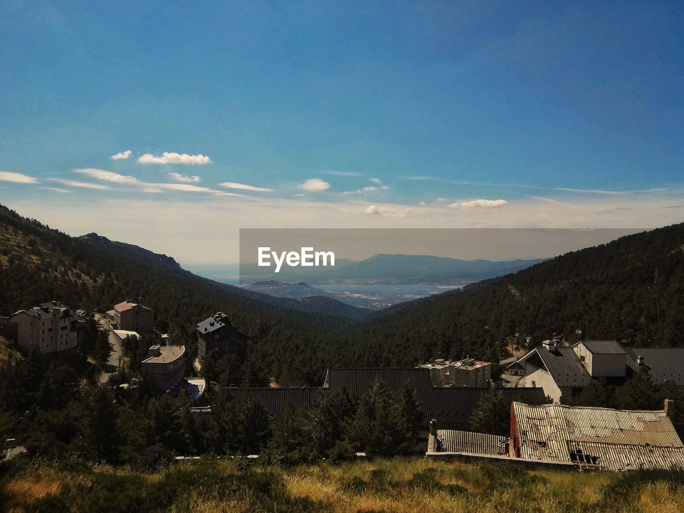 Houses by mountains against sky at puerto de navacerrada