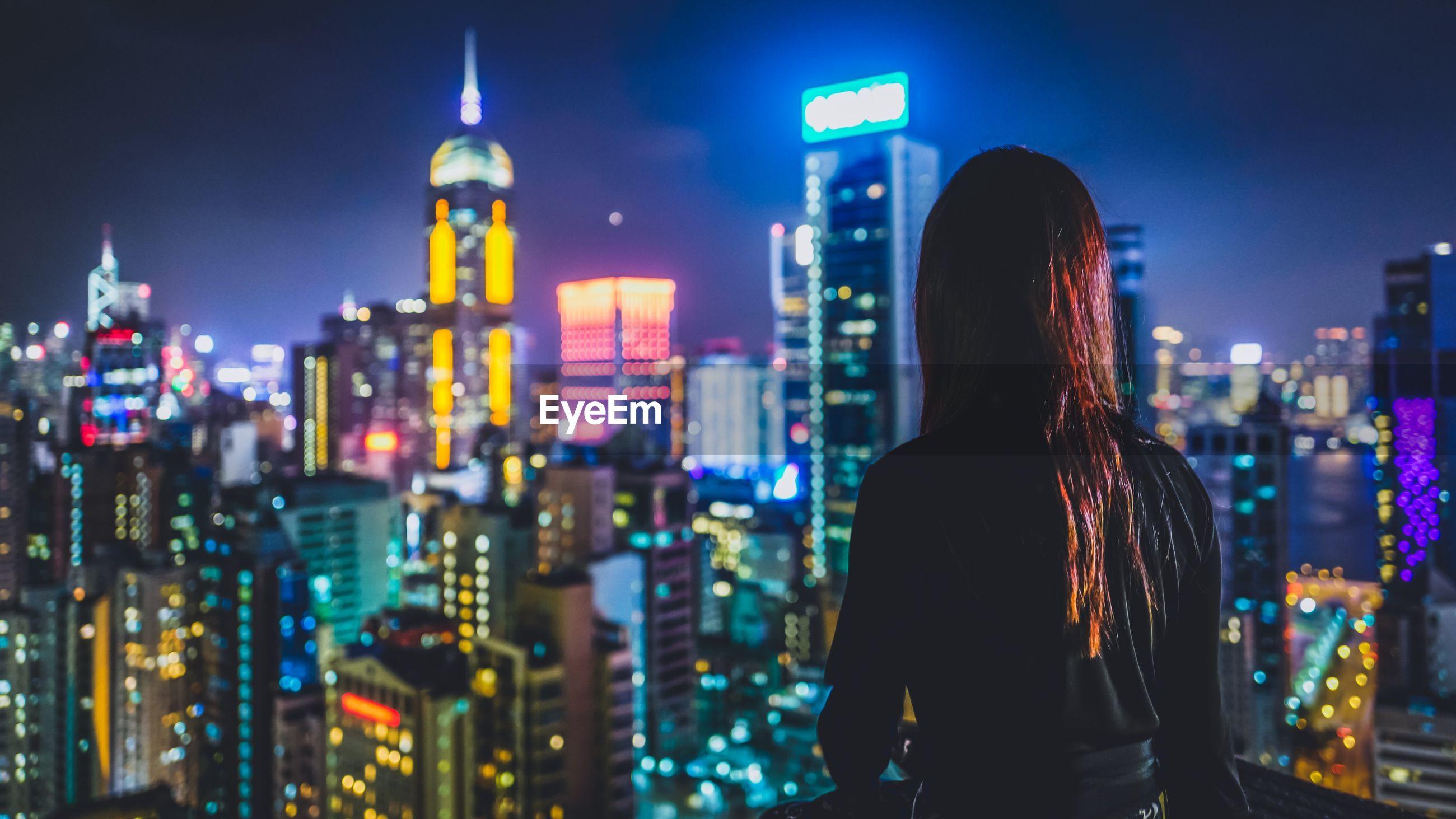Rear view of women overlooking illuminated cityscape