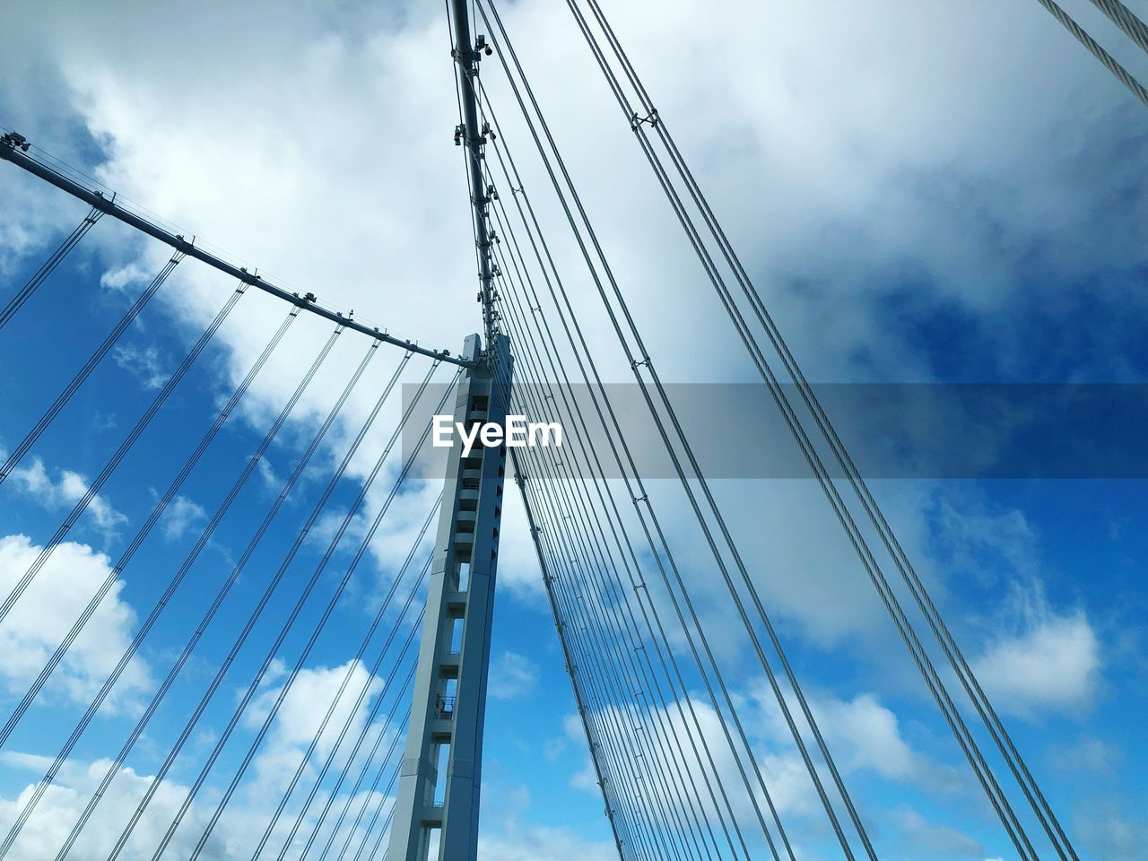 cloud - sky, low angle view, sky, cable, connection, bridge, engineering, built structure, suspension bridge, architecture, bridge - man made structure, cable-stayed bridge, transportation, day, nature, steel cable, modern, outdoors, blue, office building exterior, skyscraper, sailboat