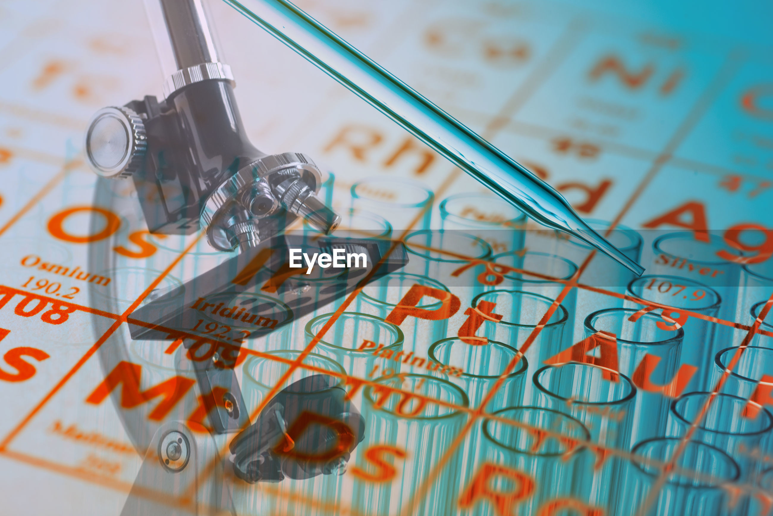 Digital composite image of periodic table over microscope and test tubes