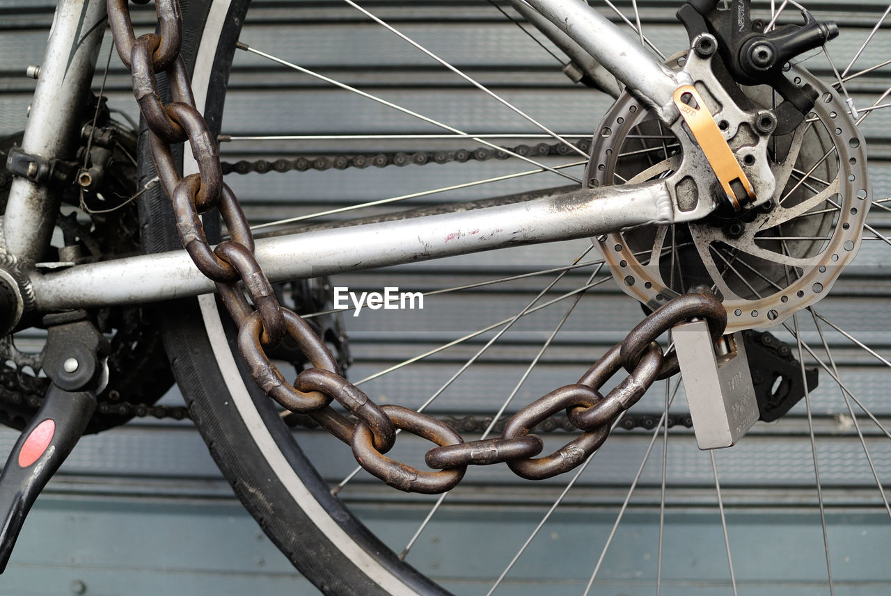 Cropped Image Of Chain Locked On Bicycle Wheel