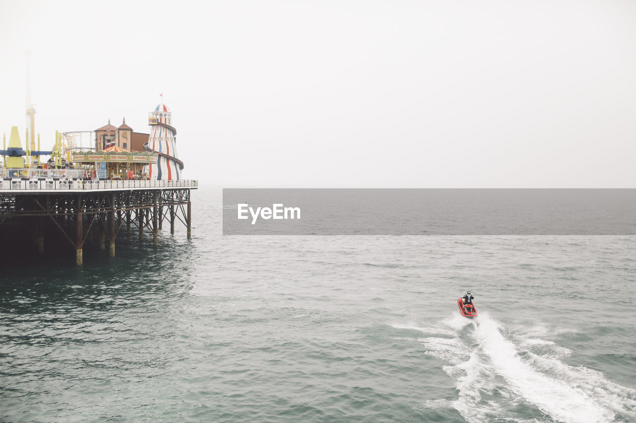 Rear View Of Man Jet Boating On Sea By Brighton Pier