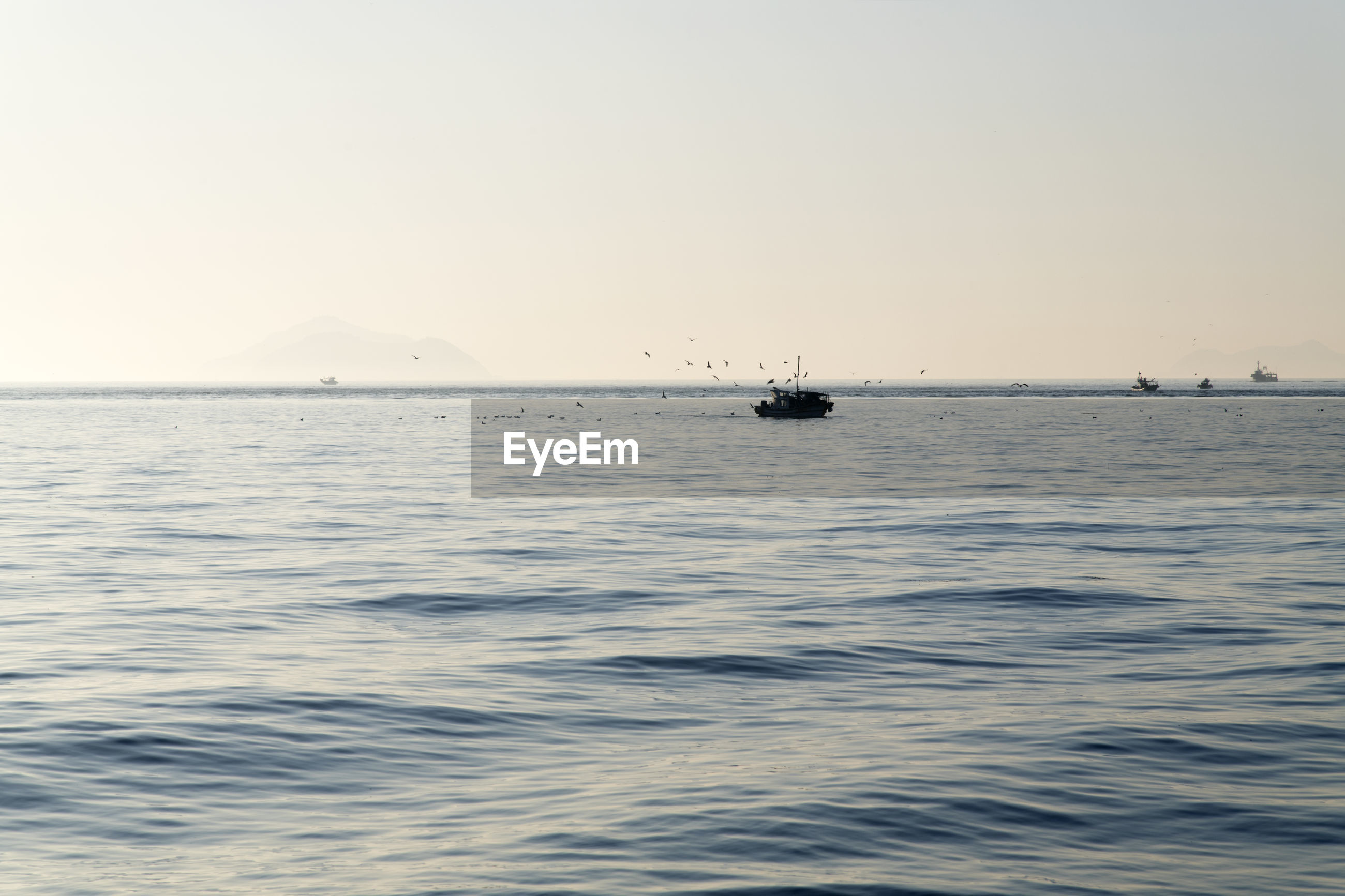 BOATS SAILING IN SEA AGAINST CLEAR SKY