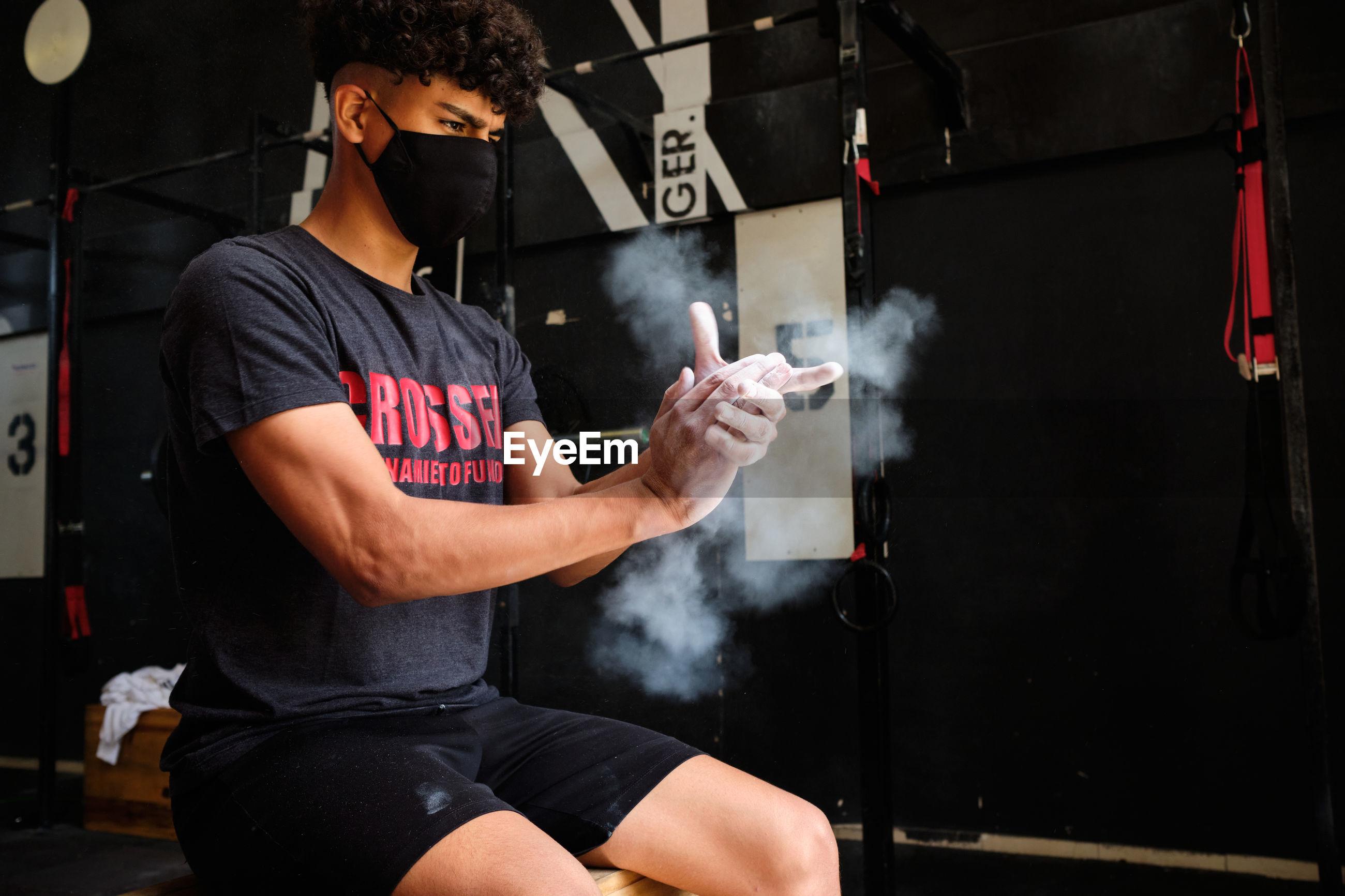 Young man wearing mask sitting at gym