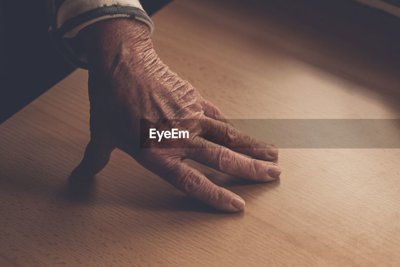 human body part, human hand, real people, hand, body part, one person, indoors, finger, human finger, unrecognizable person, lifestyles, close-up, high angle view, relaxation, human leg, low section, men, barefoot, flooring, human foot, human limb