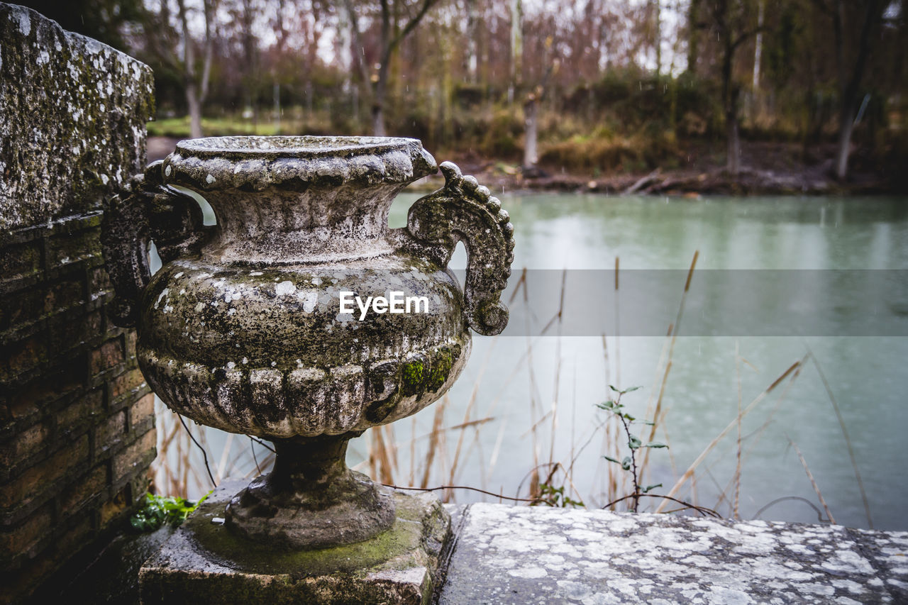 water, lake, focus on foreground, day, nature, no people, plant, reflection, outdoors, solid, close-up, architecture, art and craft, tree, fountain, animal themes, old, stone material, flowing water