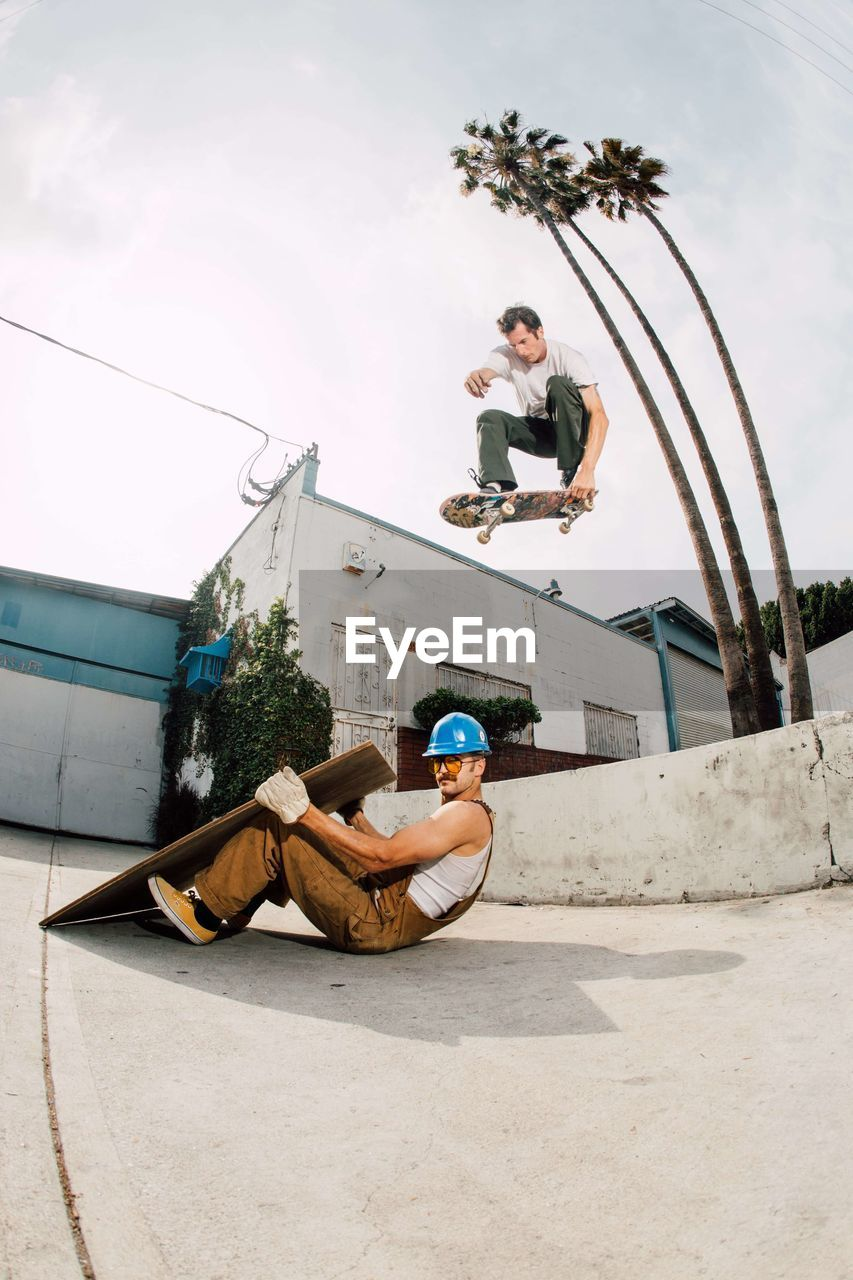 full length, real people, lifestyles, sky, people, young adult, casual clothing, leisure activity, architecture, day, young women, young men, men, nature, front view, outdoors, built structure, skateboard park, skill