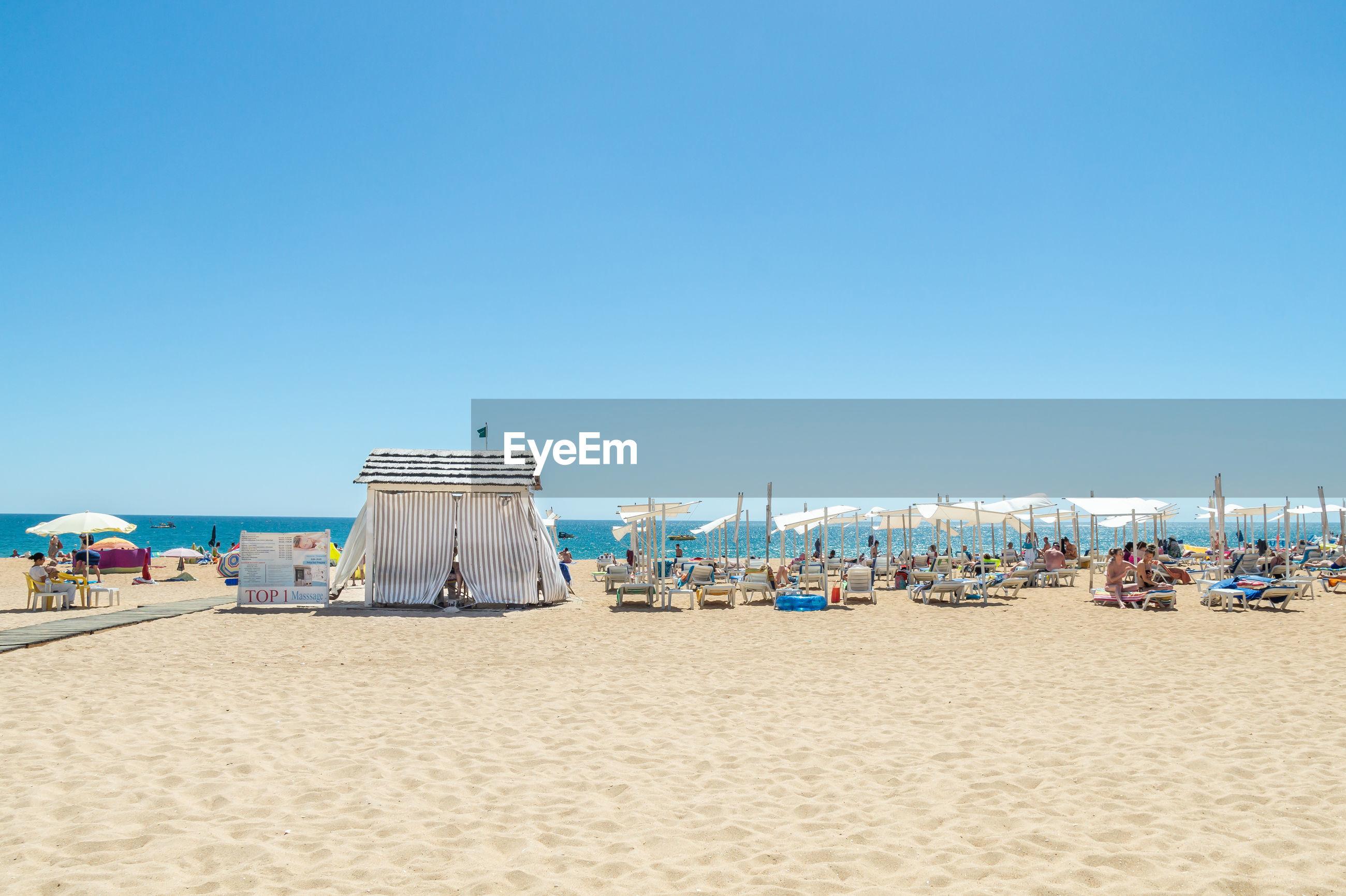 HOODED BEACH CHAIRS AGAINST CLEAR SKY