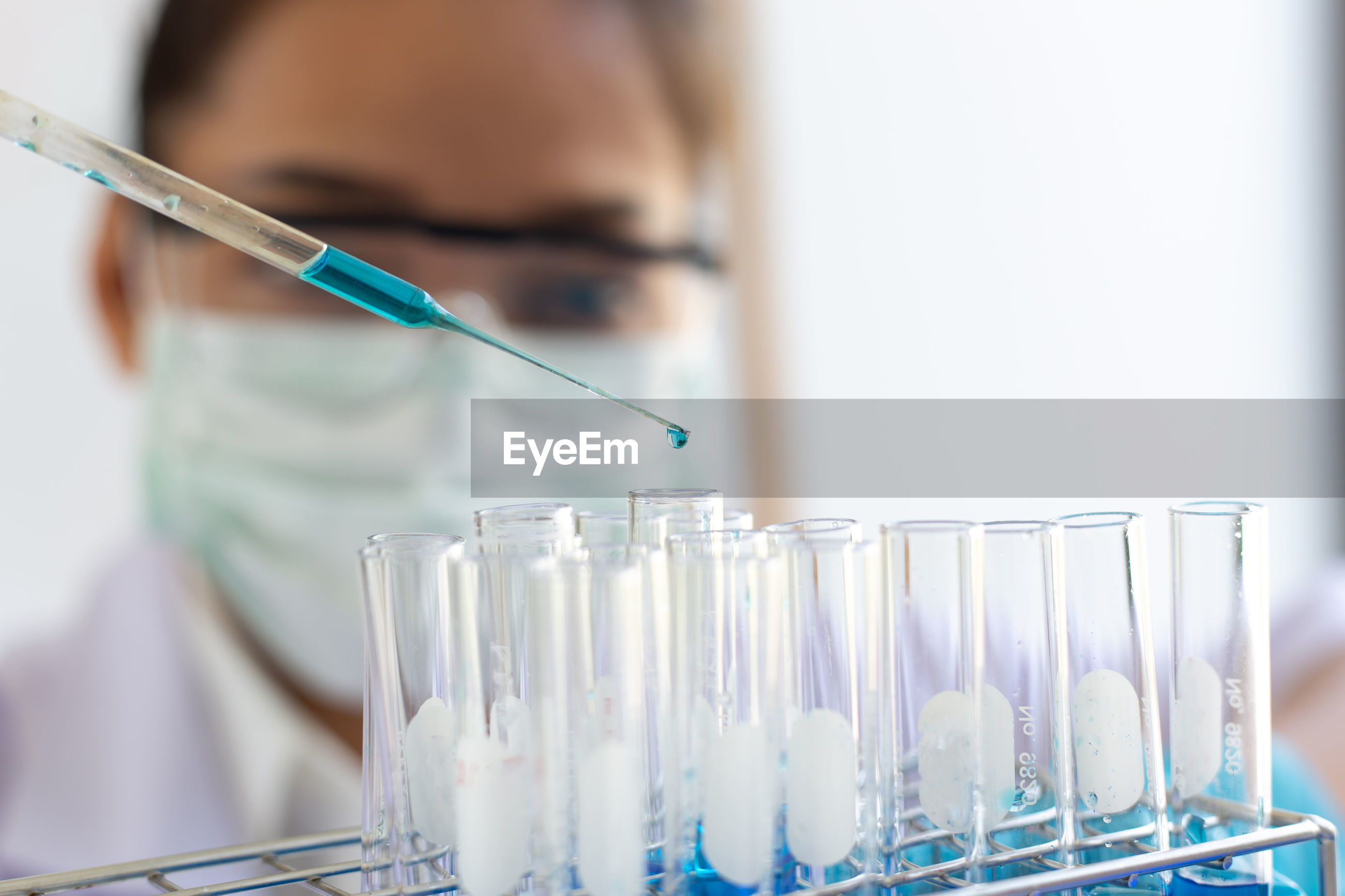 Close-up of female scientist doing pipetting liquid in test tubes