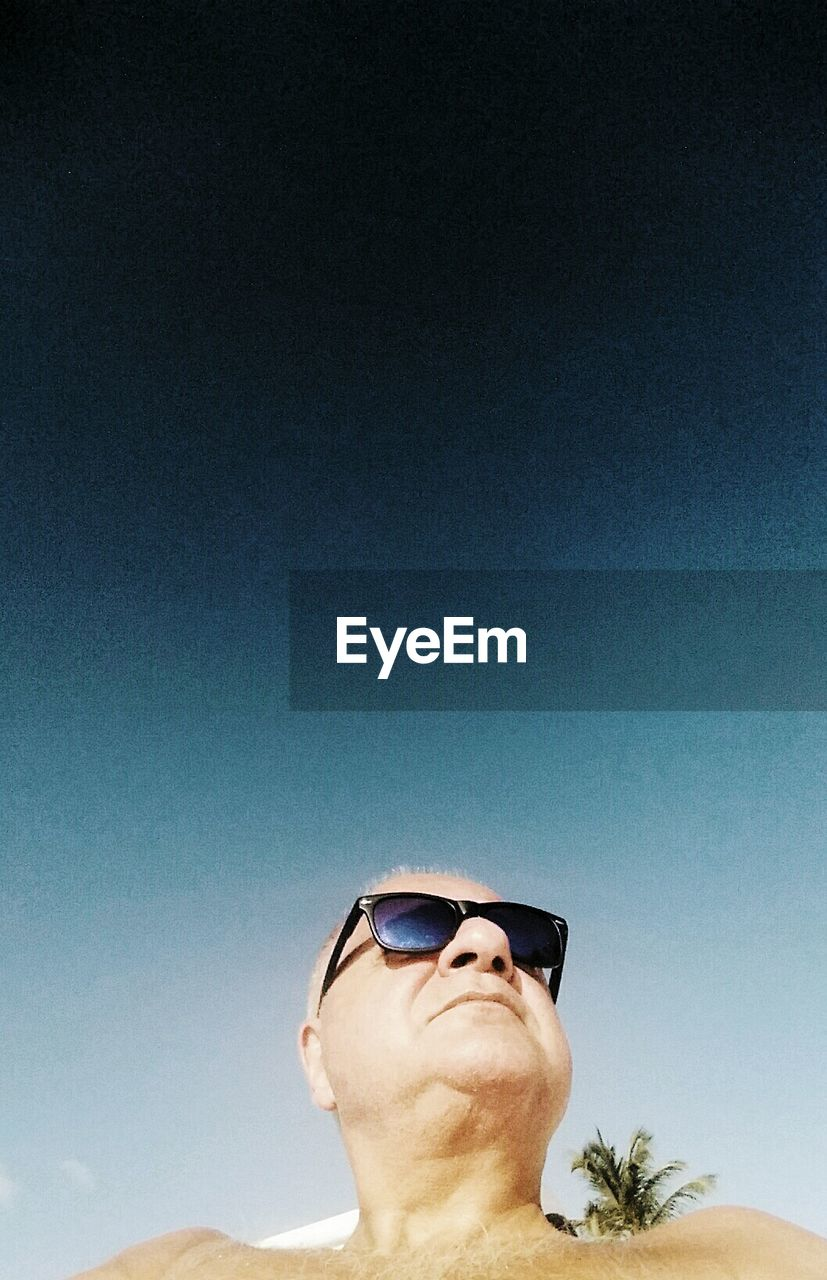 Close-Up Portrait Of Man Wearing Sunglasses Against Sky