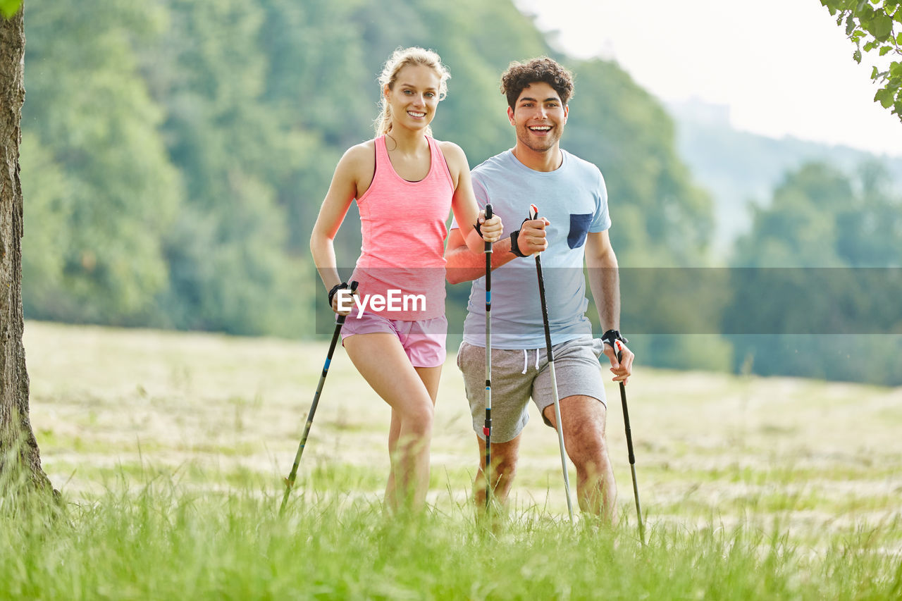 Young Man And Woman Running With Hiking Poles On Field In Park