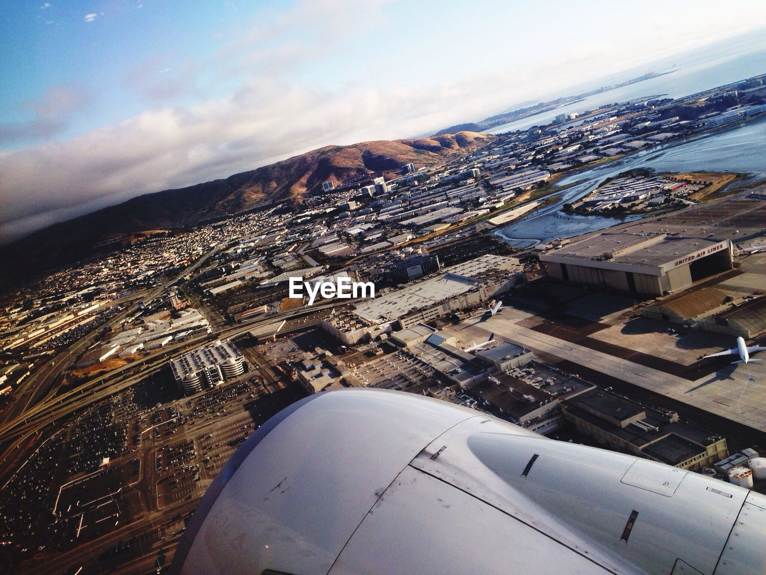 aerial view, airplane, building exterior, air vehicle, cityscape, sky, architecture, aircraft wing, built structure, city, high angle view, cloud - sky, landscape, mode of transport, transportation, crowded, part of, mountain, flying, travel