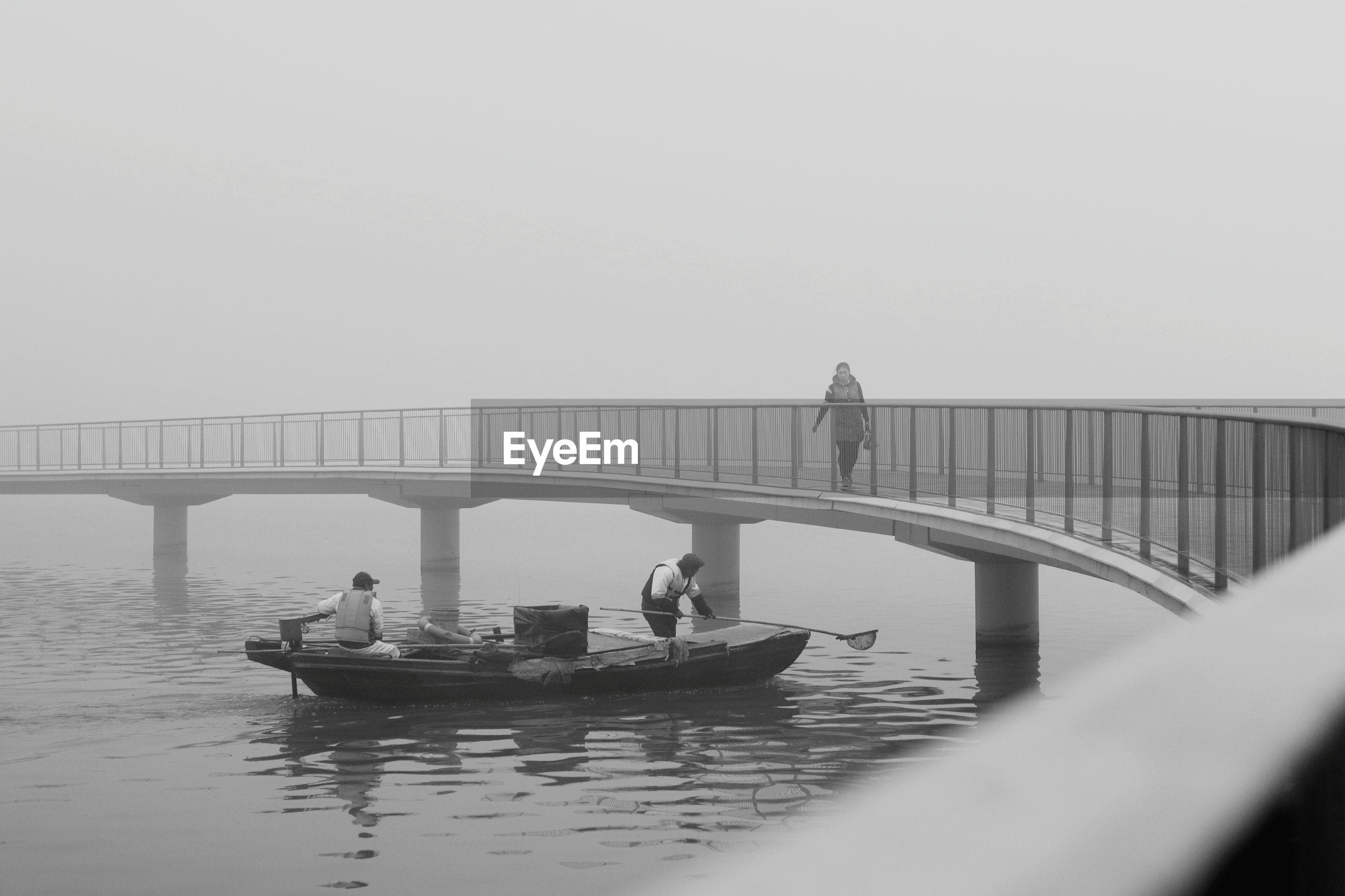 People fishing in boat on lake while woman walking on footbridge against sky