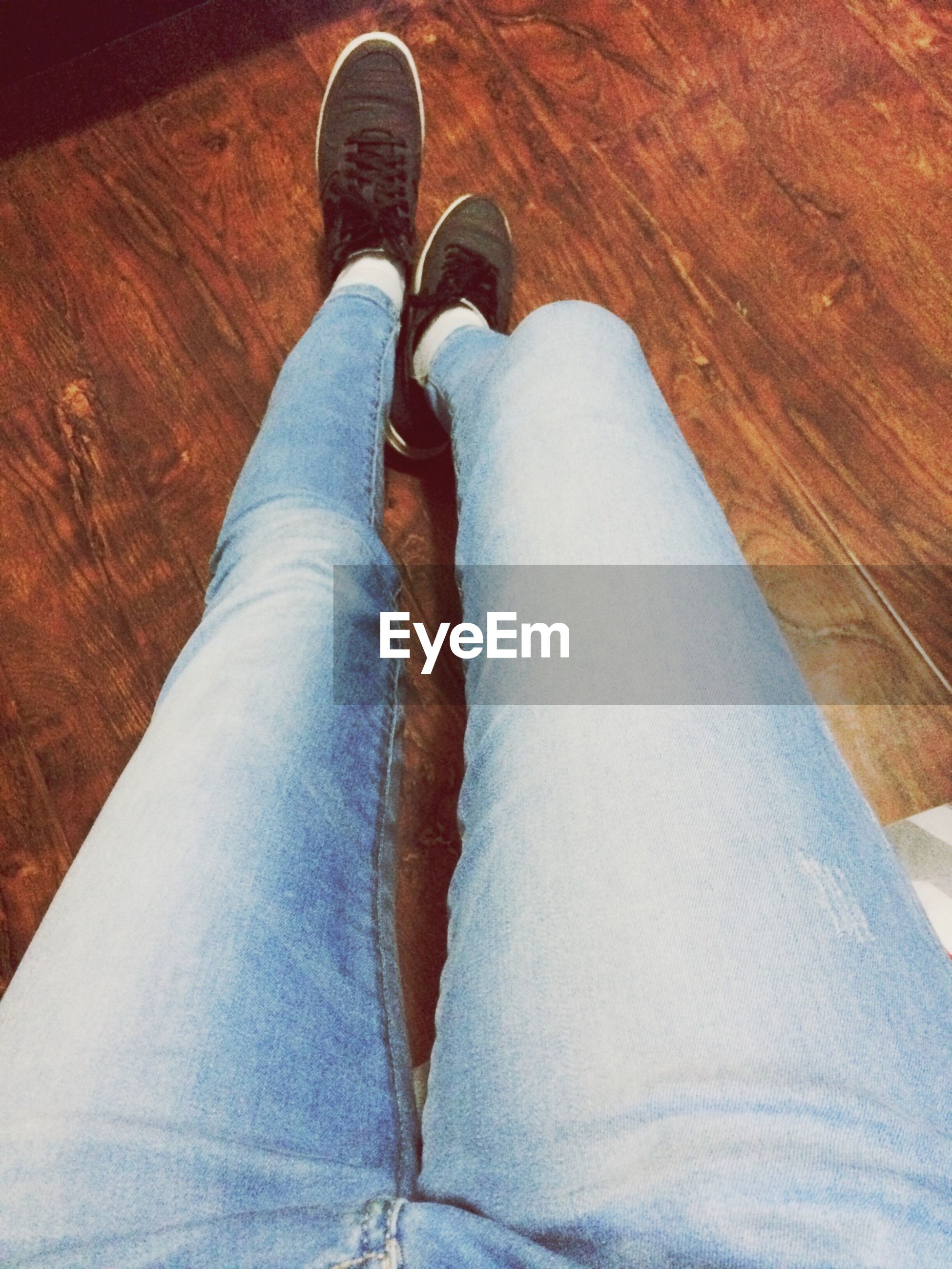 low section, person, shoe, indoors, high angle view, jeans, footwear, personal perspective, human foot, relaxation, canvas shoe, hardwood floor, pair, directly above, close-up, leather, sock